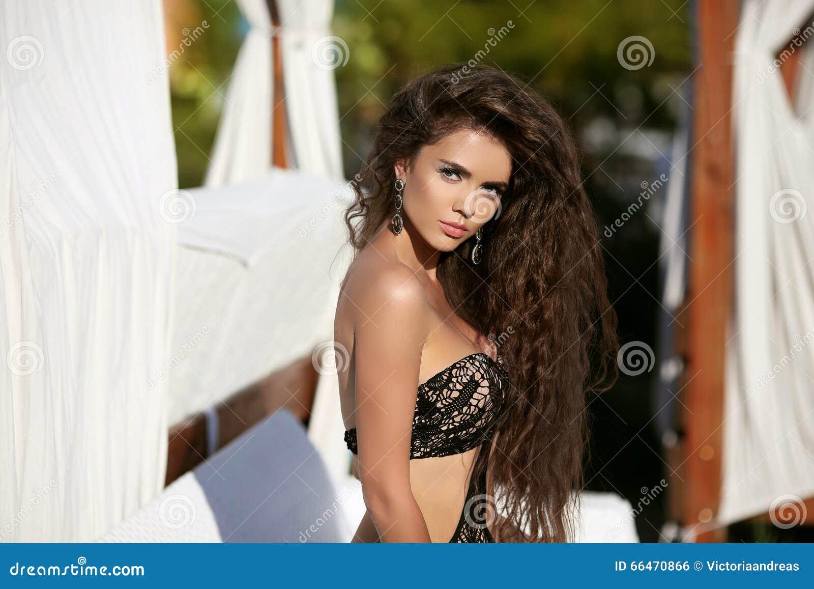Mooi sexy vrouwenmodel met lang golvend haar in zwarte bikini p
