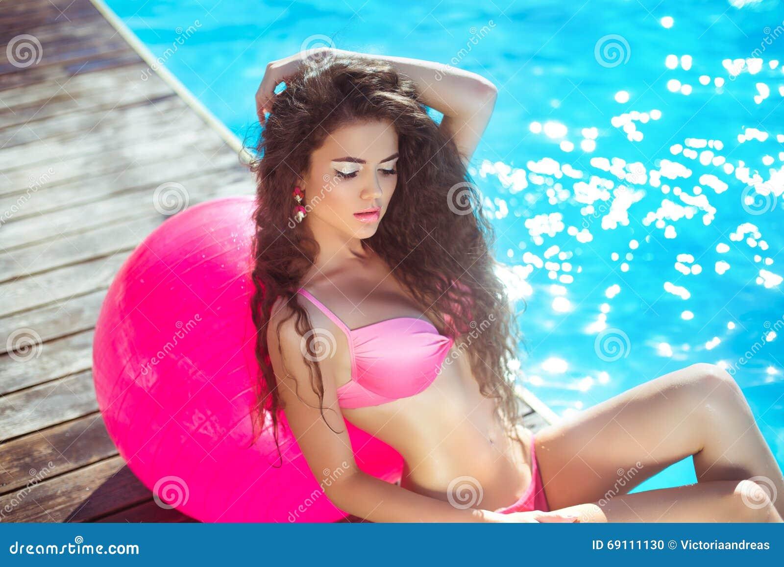 Mooi sexy vrouwenmodel in roze bikini met pilates fitball p