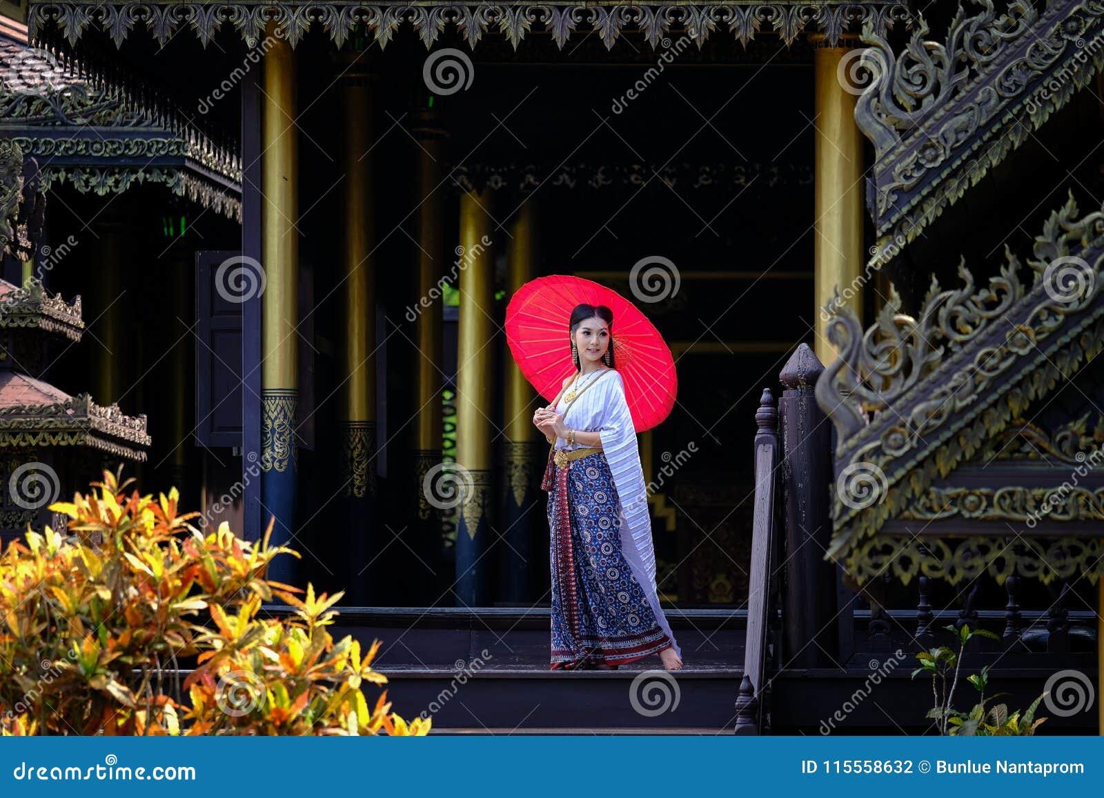 Mooi Thais meisje in de traditionele rode paraplu van het kledingskostuum zoals