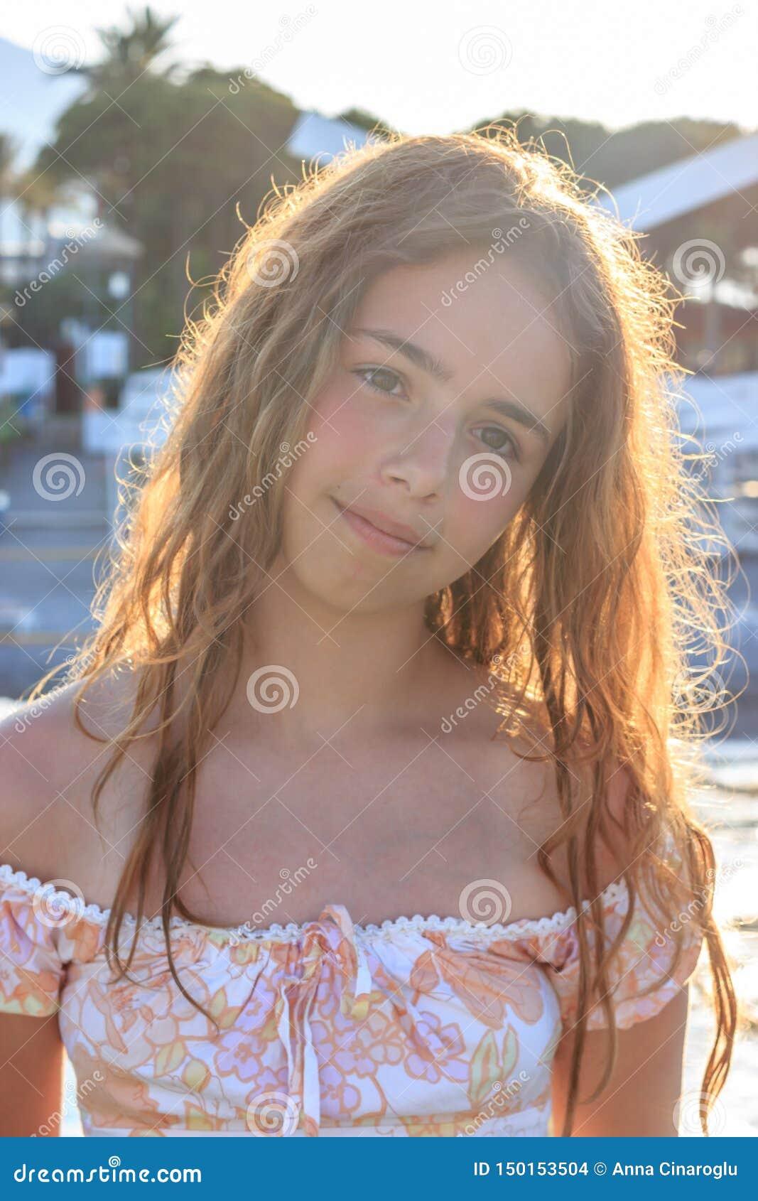 Mooi tienermeisje in de stralen van de het plaatsen zon op een pijler door het overzees