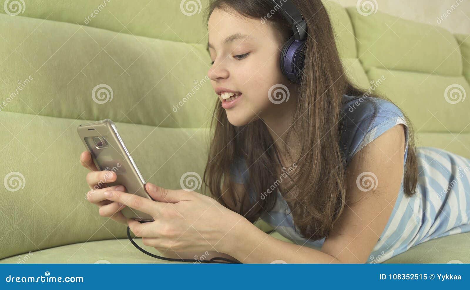 Mooi tienermeisje in hoofdtelefoons die karaokeliederen in smartphone zingen