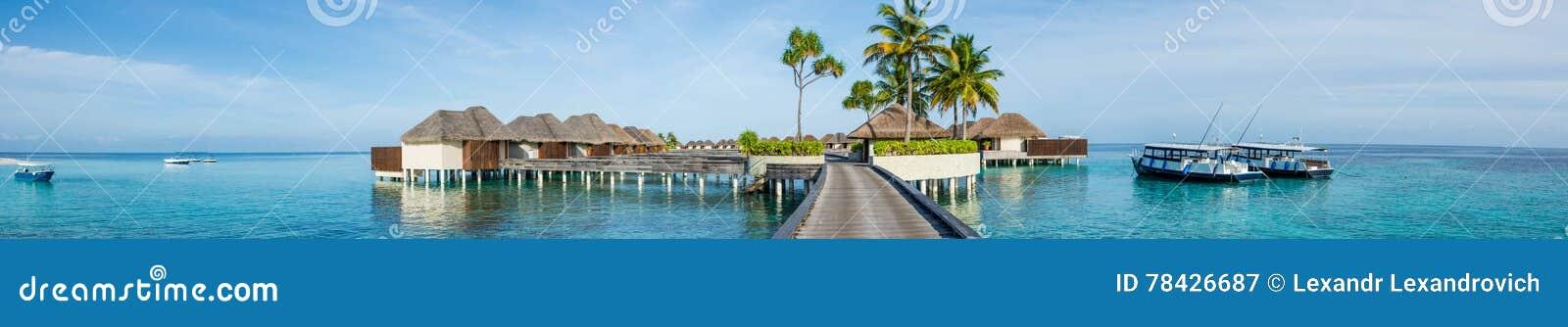 Mooi tropisch strandpanorama van bungalos met brug dichtbij de oceaan met palmenbomen en boten in de Maldiven