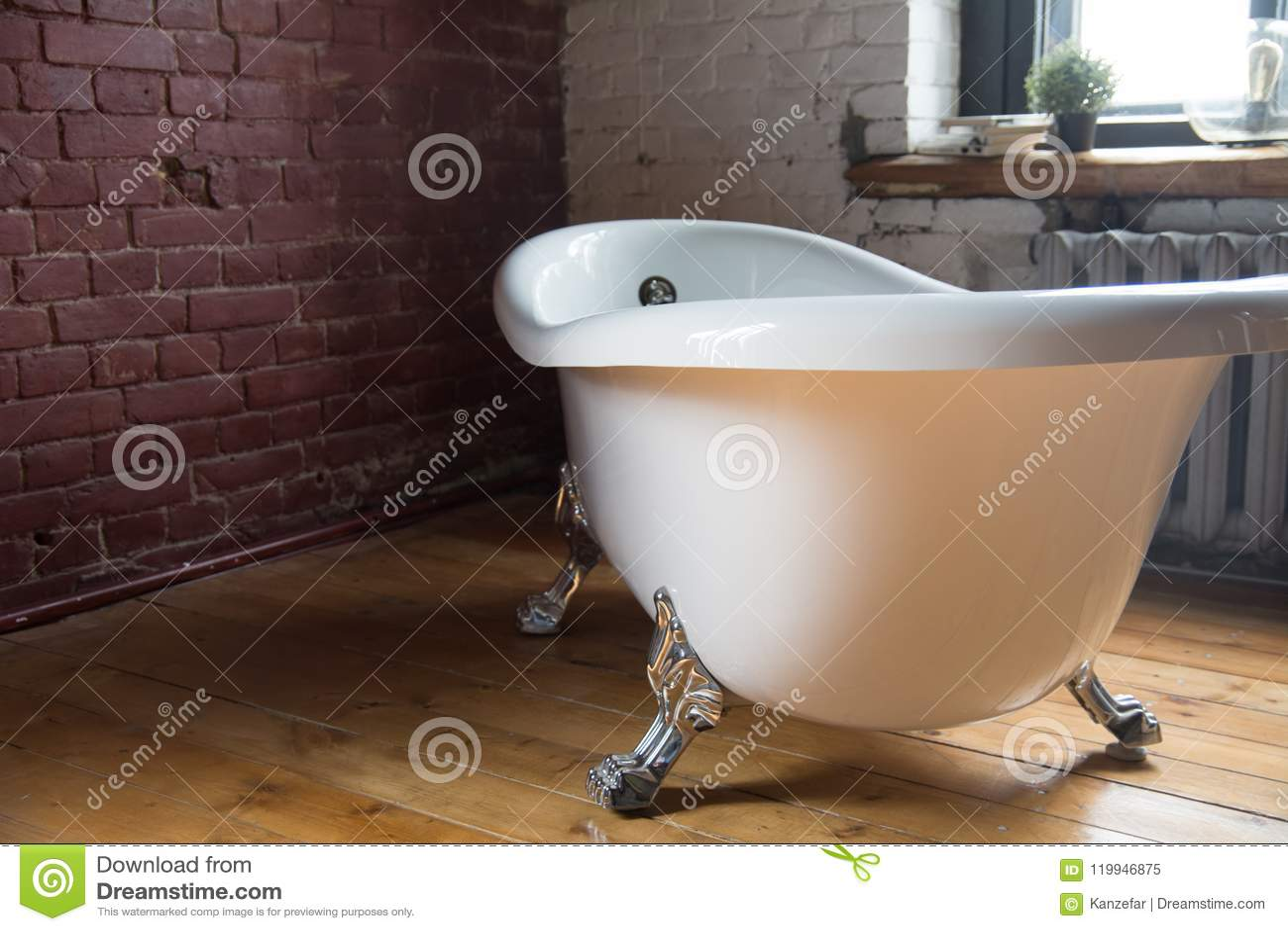 Mooi uitstekend bad op een houten vloer tegen een bakstenen muur