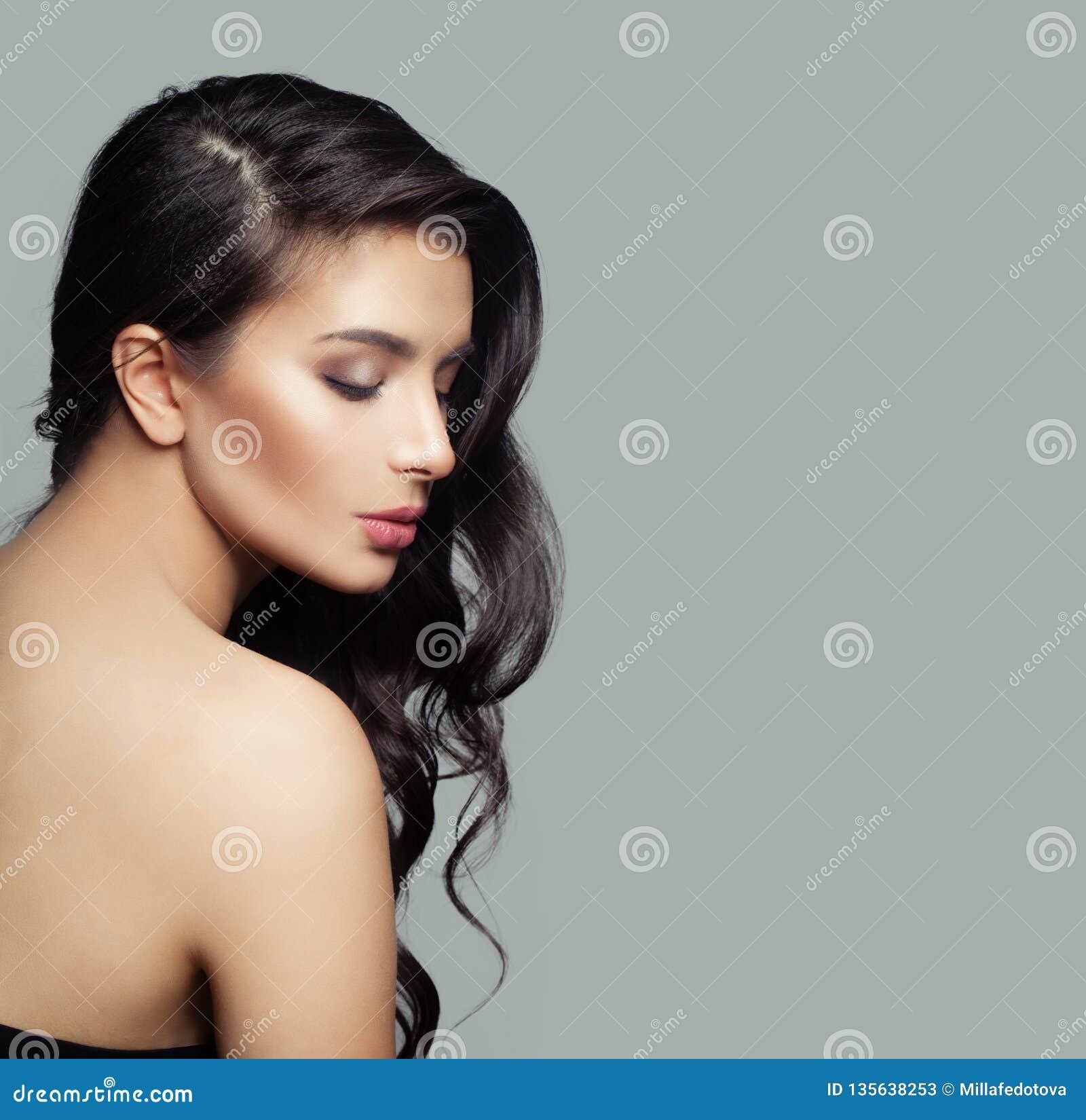 Mooi vrouwelijk profiel Leuke donkerbruine vrouw met natuurlijke make-up en lang zwart haar op grijze achtergrond