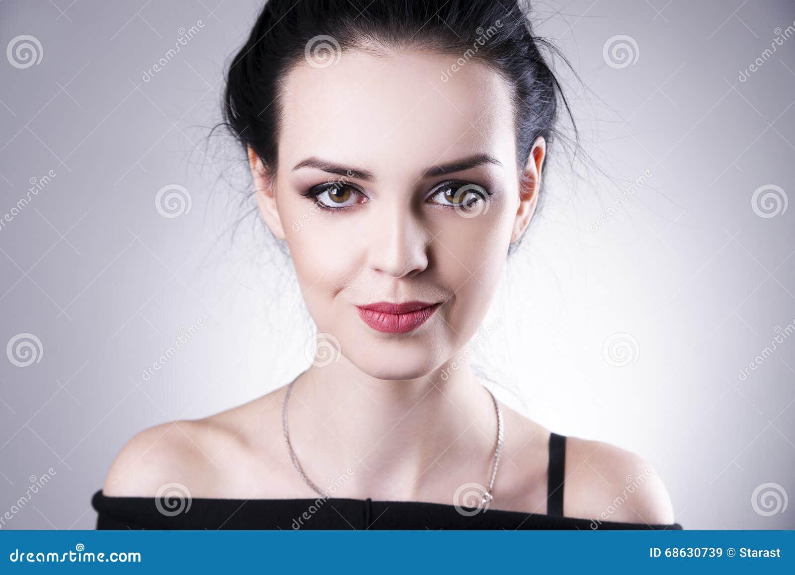 Mooi vrouwenportret op een grijze achtergrond Professionele Make-up