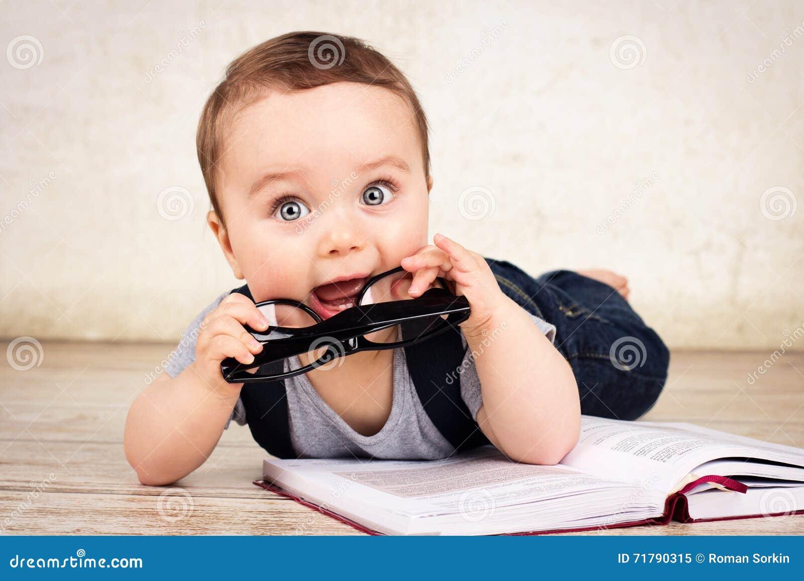 Mooi weinig babyjongen die met glazen een boek lezen