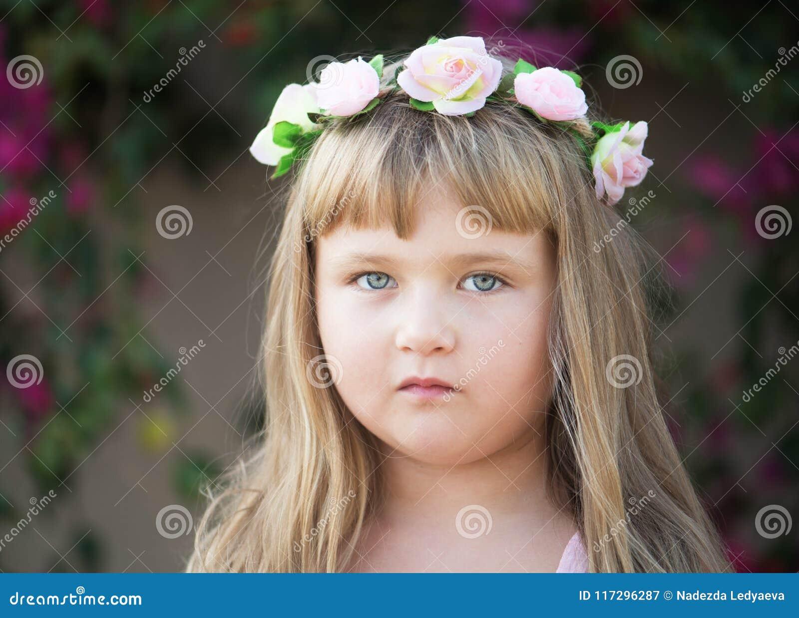 Mooi weinig babymeisje met madeliefjekroon op haar hoofd