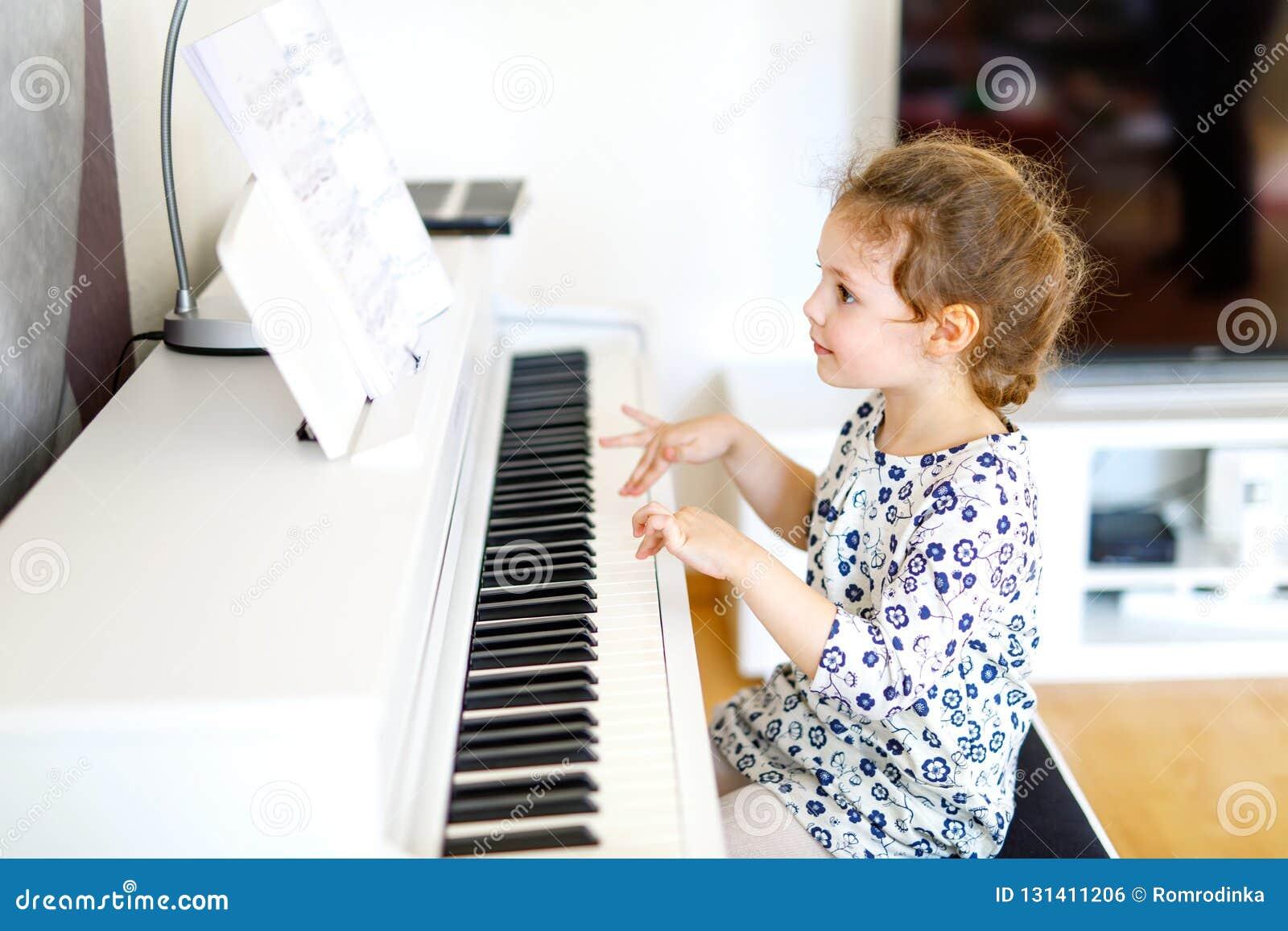 Mooi weinig jong geitjemeisje het spelen piano in woonkamer of muziekschool Peuterkind die pret met het leren hebben te spelen