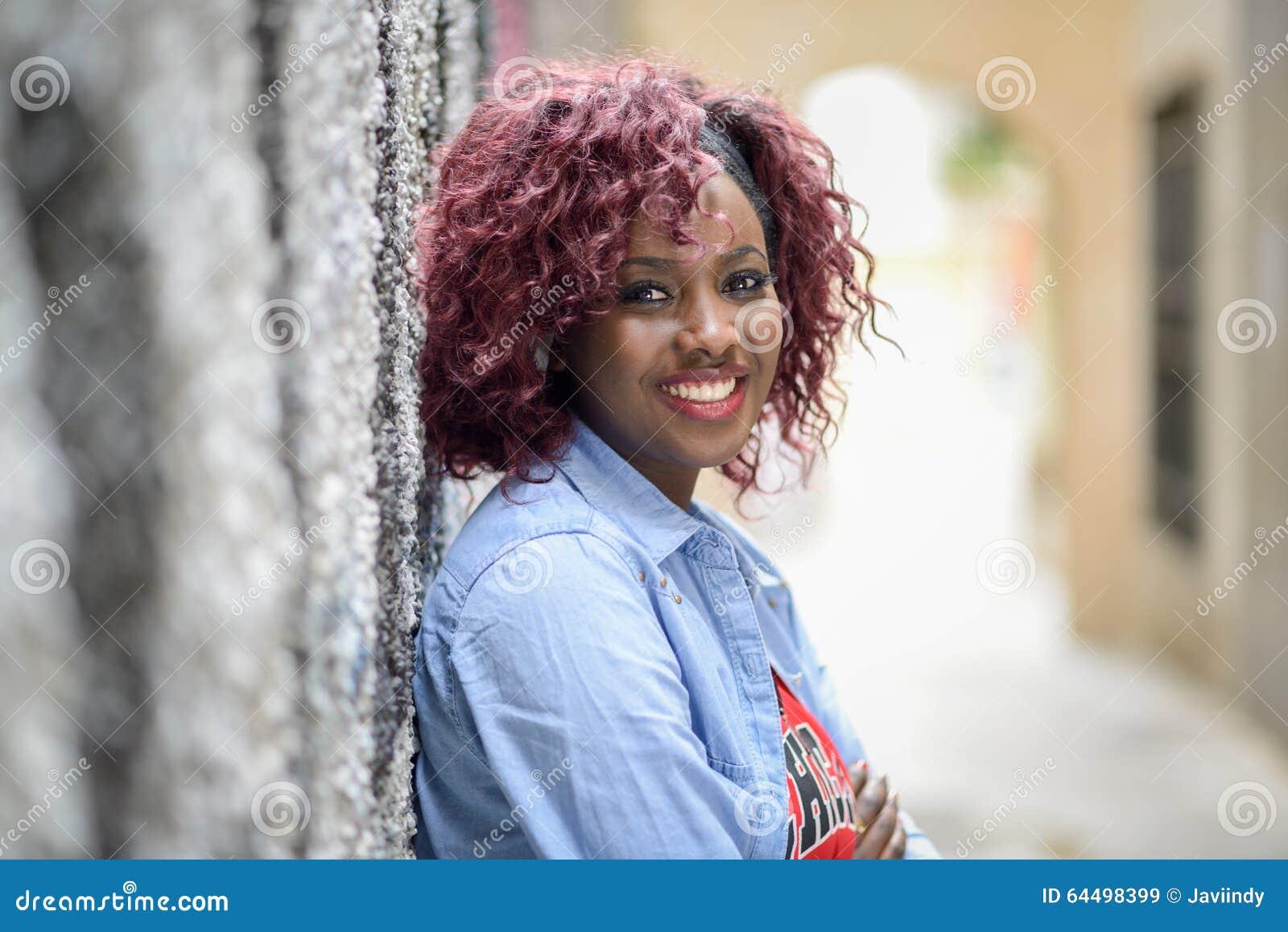 Mooi zwarte op stedelijke achtergrond met rood haar
