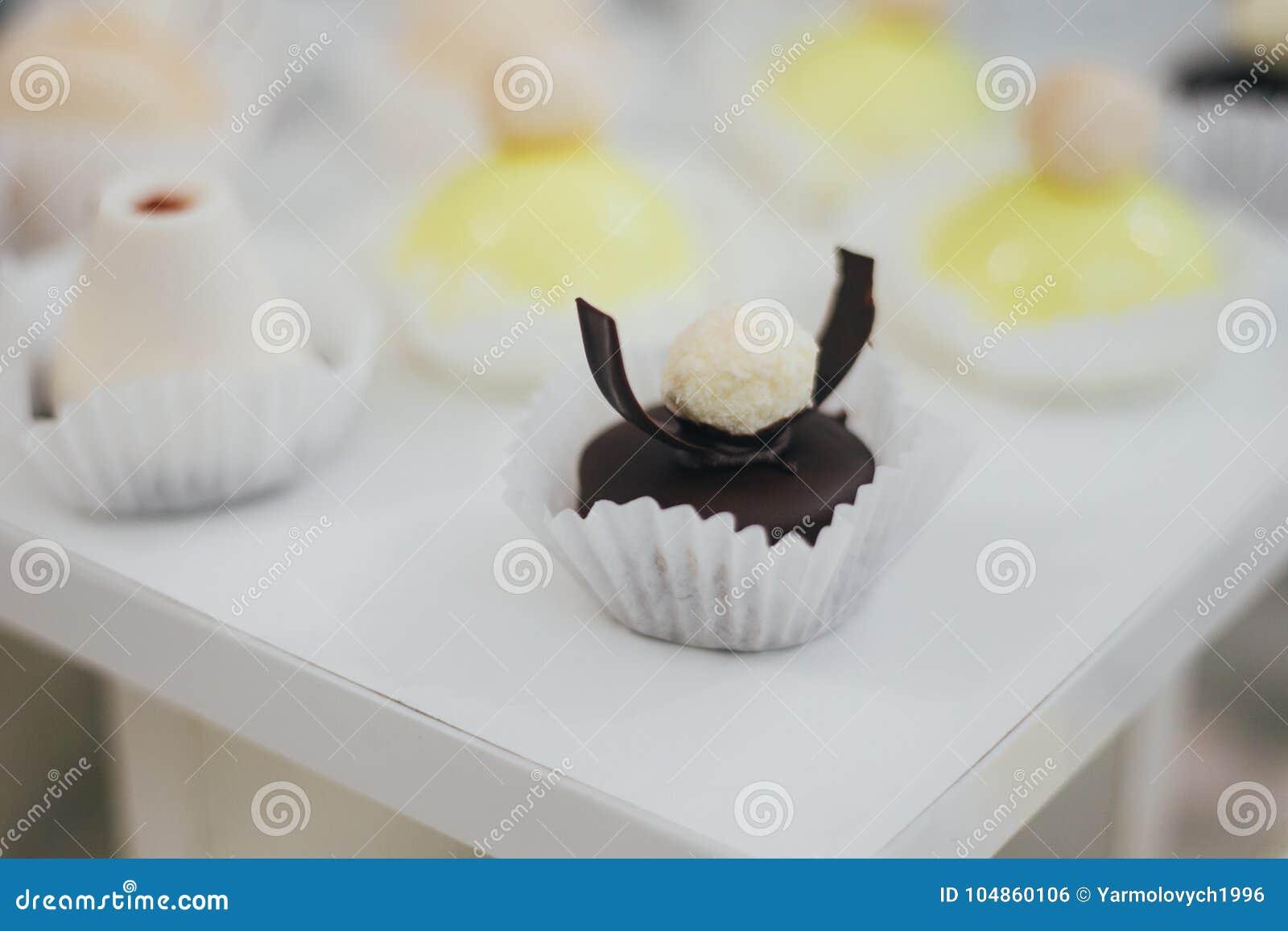 Mooie aanbiddelijke vier éénjarigenjongen, die zijn verjaardag vieren, blazend kaarsen op eigengemaakte gebakken cake, binnen Ver