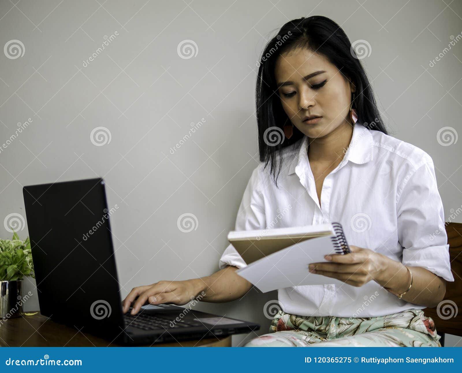 Mooie Aziatische freelancer die notaboek, dat op labtoptoetsenbord typt concentreert haar werk kijkt