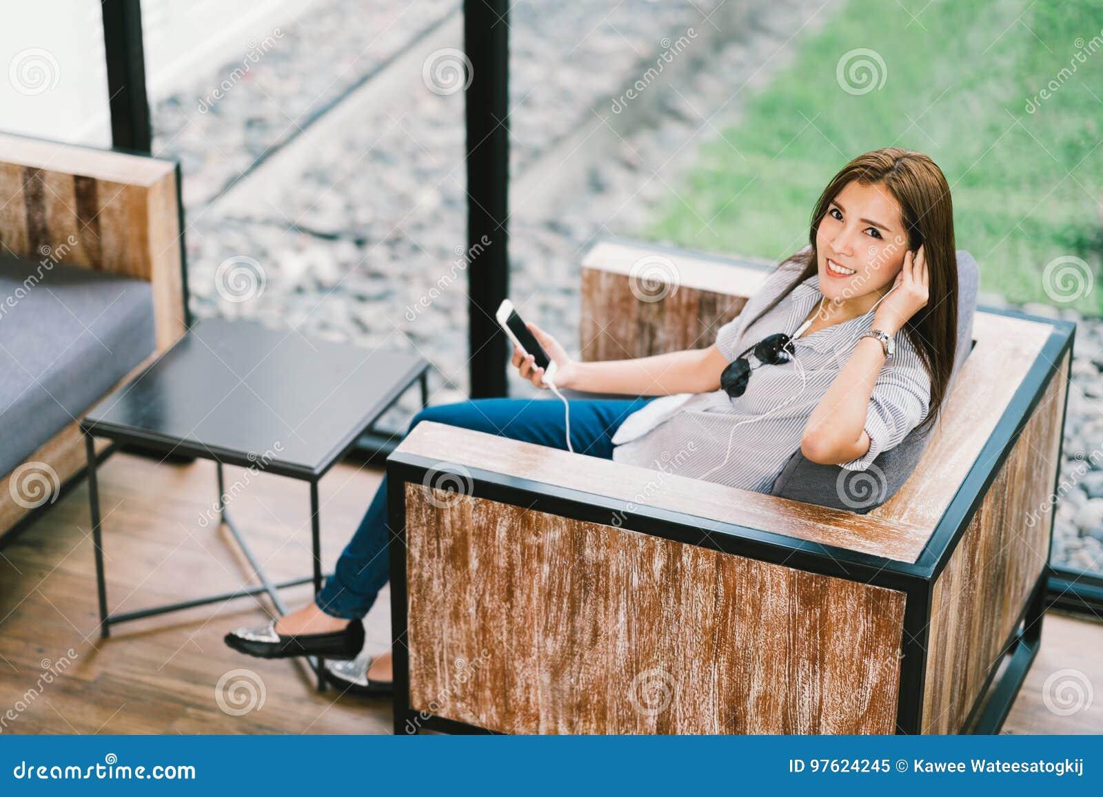 Mooie Aziatische vrouw die aan muziek luisteren die smartphone gebruiken, zittend in koffie of koffiewinkel Het ontspannende conc