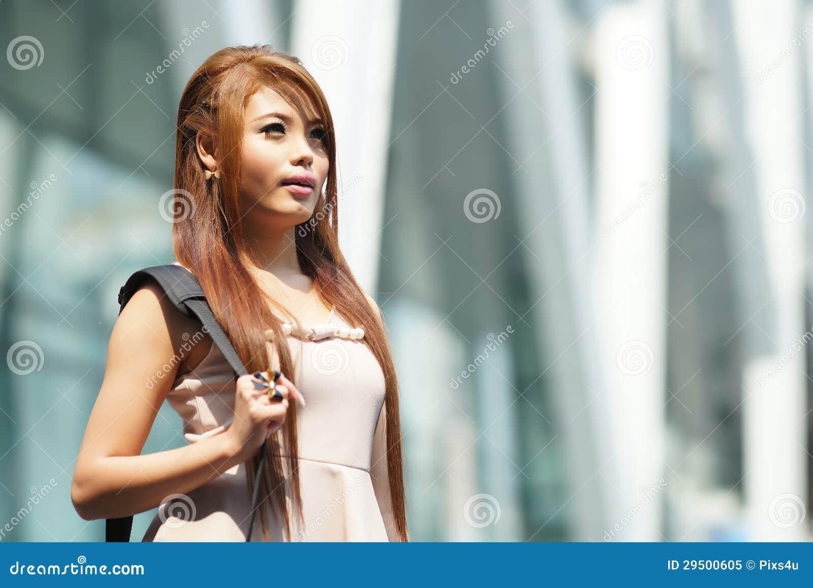 Mooie bedrijfsvrouw die buiten haar bureau met aktentas lopen