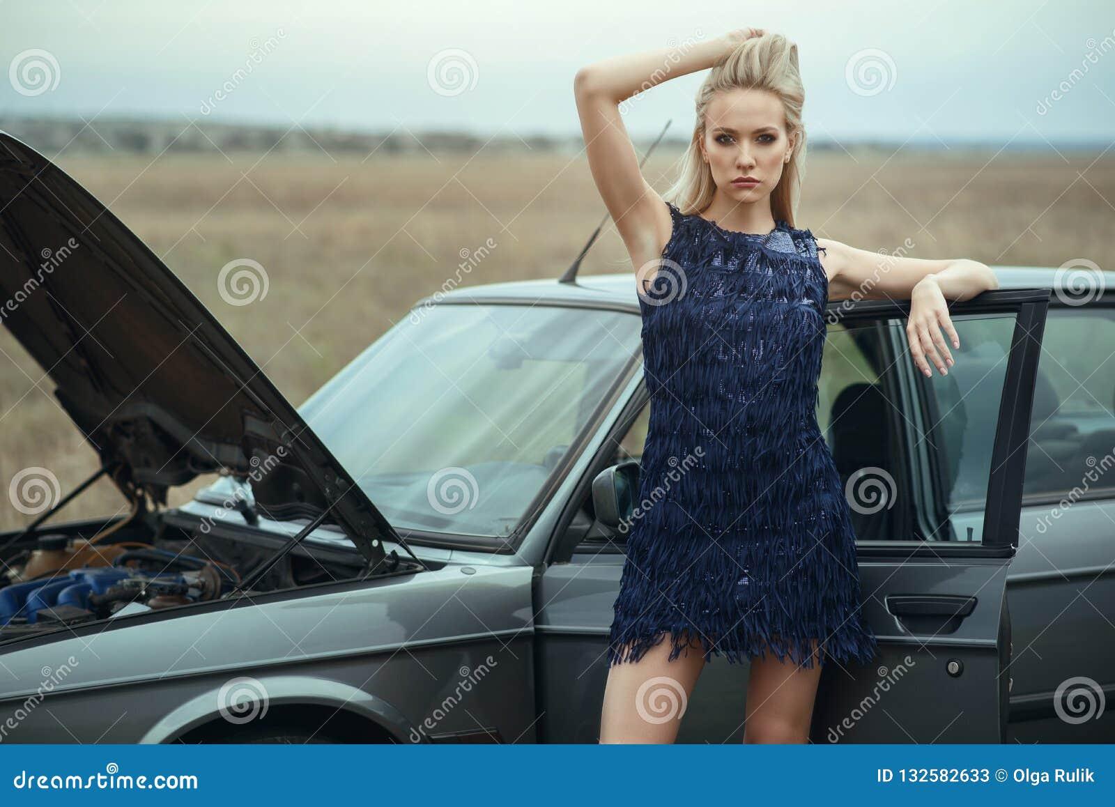 Mooie blonde dame in de luxueuze donkerblauwe avondjurk die van de lovertjeleeswijzer zich bij haar oude auto met open kap bevind