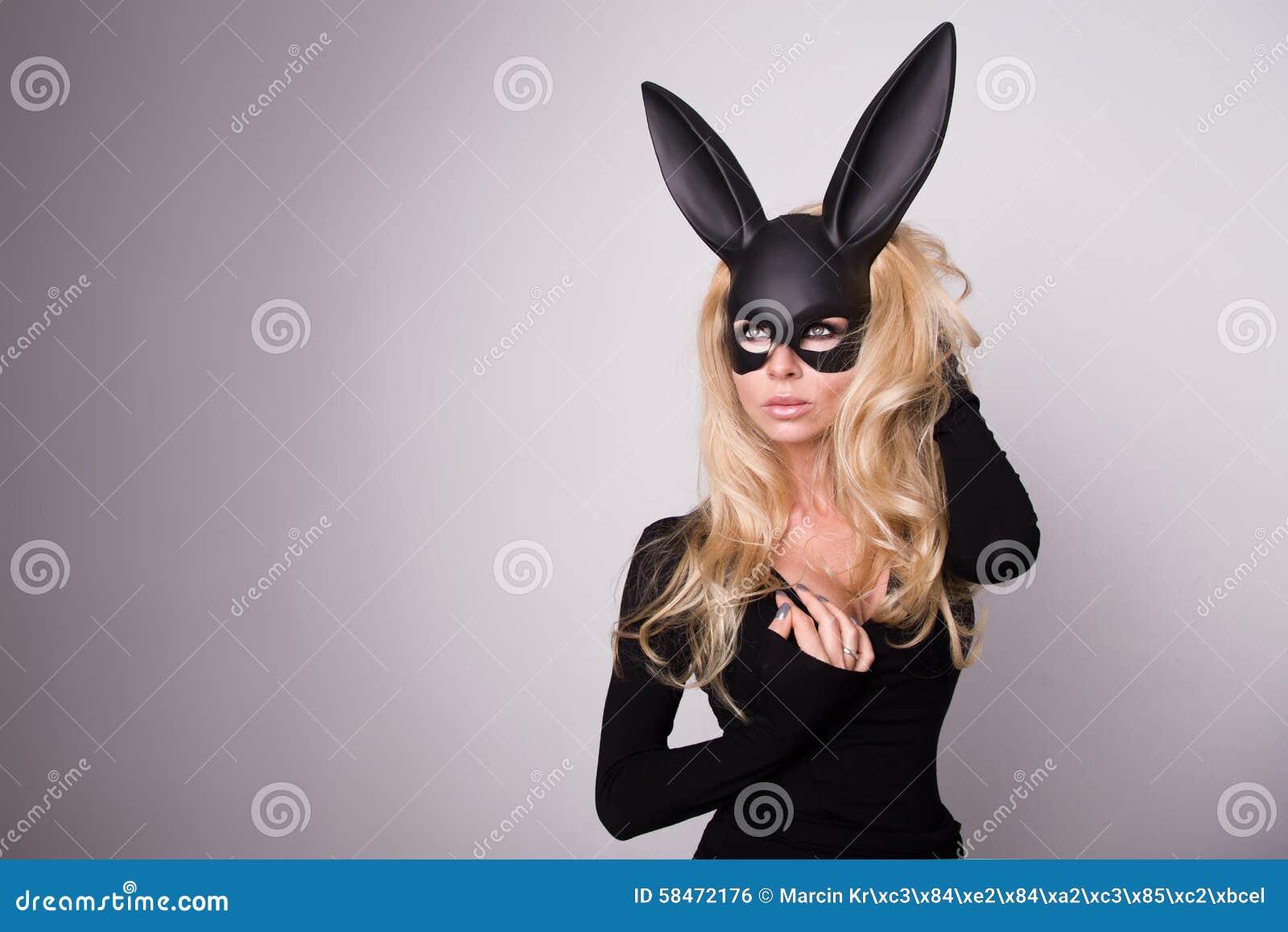 Mooie blonde-haired jonge vrouw bij Carnaval-het konijn van de maskerbalzaal met lange oren sensuele sexy in een zwarte kleding