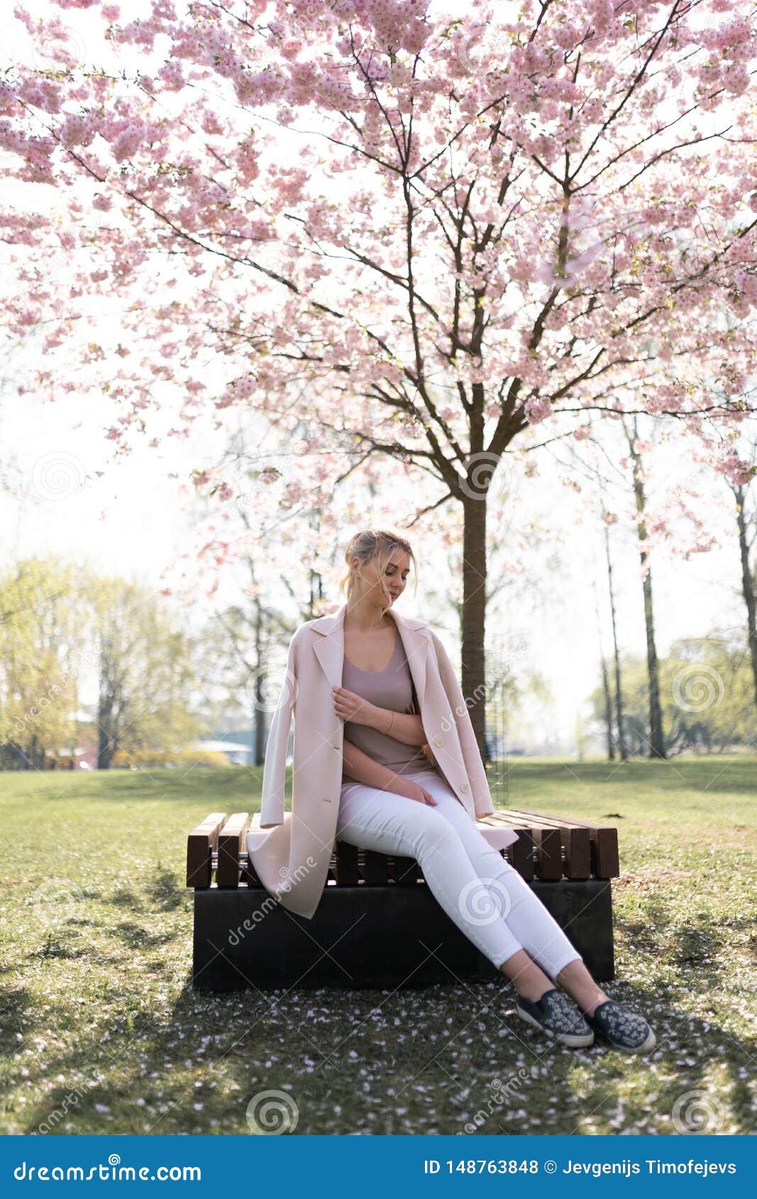 Mooie blonde jonge vrouw die in Sakura Cherry Blossom-park in de Lente van aard en vrije tijd genieten tijdens haar die reizen