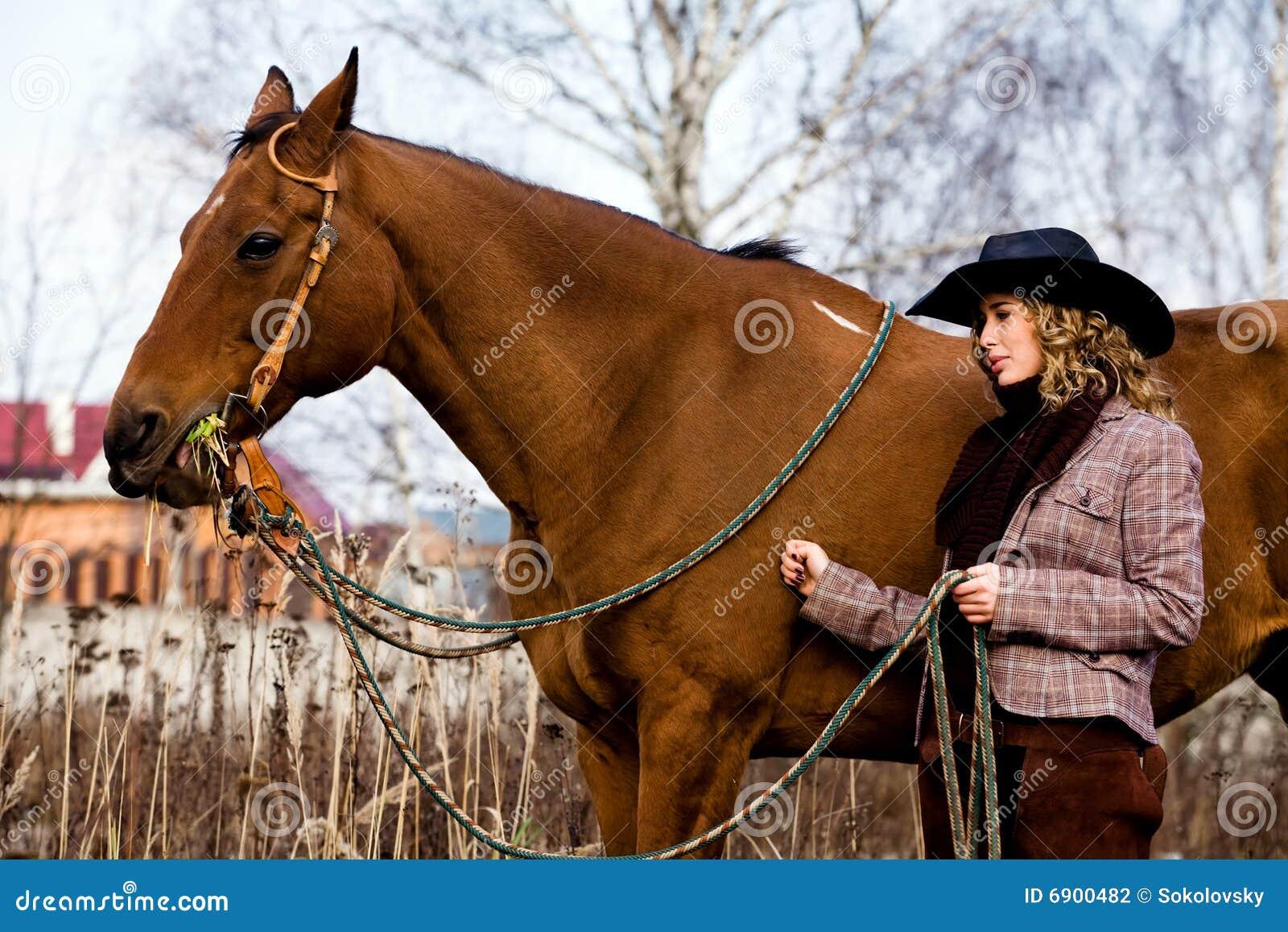 Mooie blonde vrouw in een hoed die zich door paard bevindt