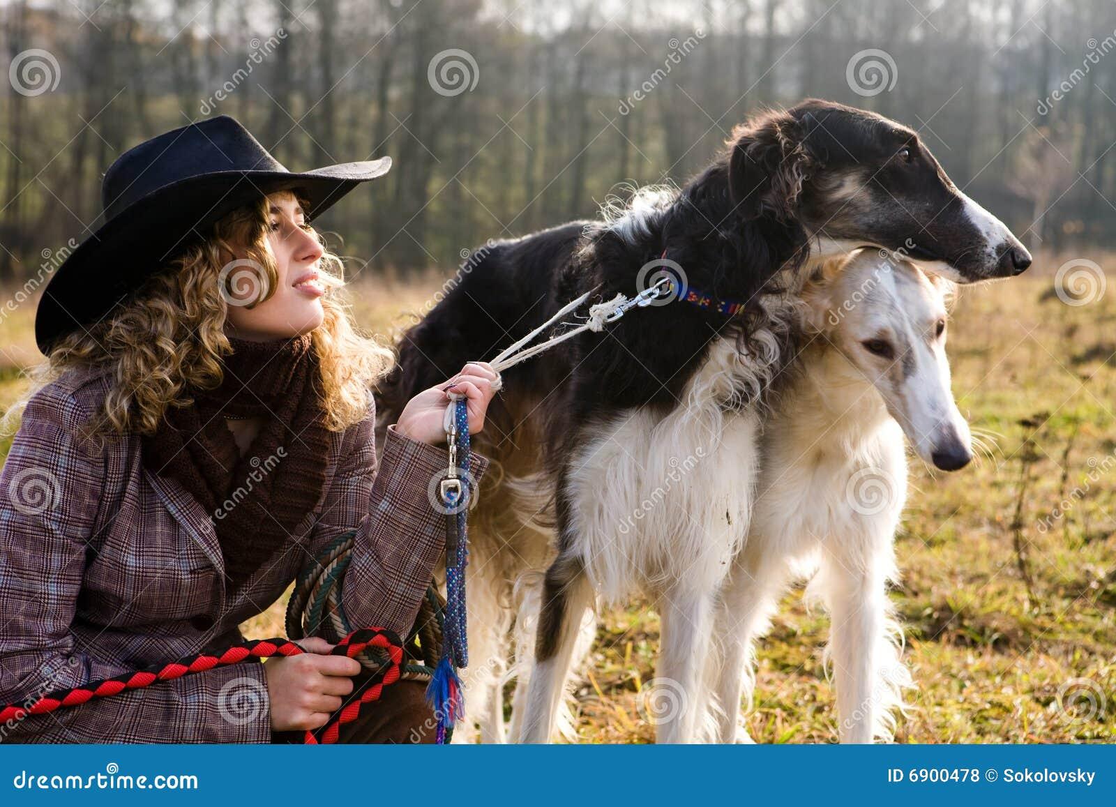Mooie blonde vrouw met twee honden op een gebied