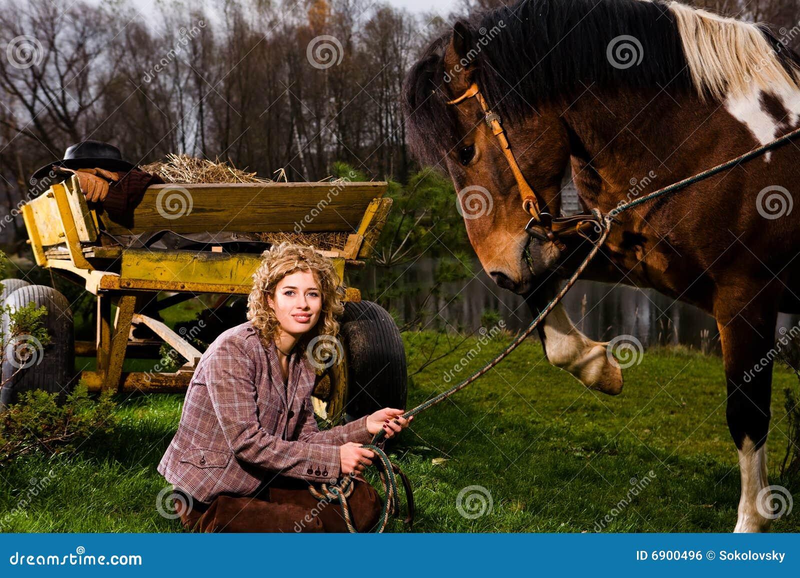 Mooie blonde vrouwenzitting door paard