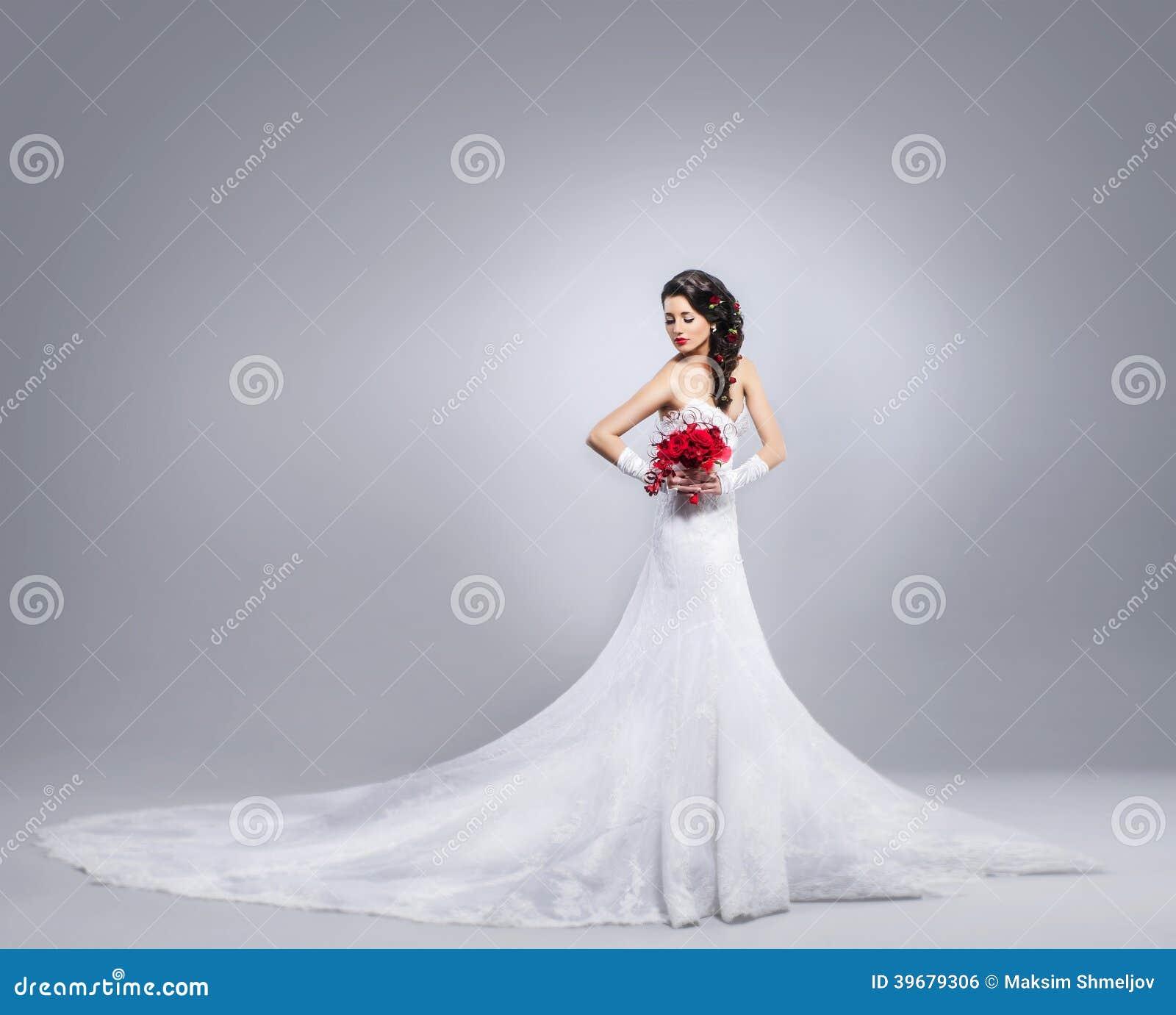 Mooie bruid die zich met een bloemboeket bevinden