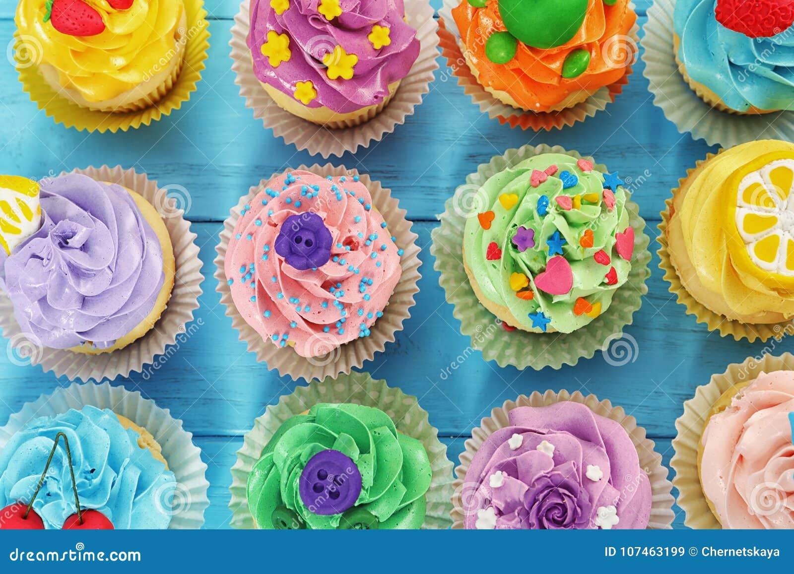 Mooie cupcakes op kleuren houten achtergrond,