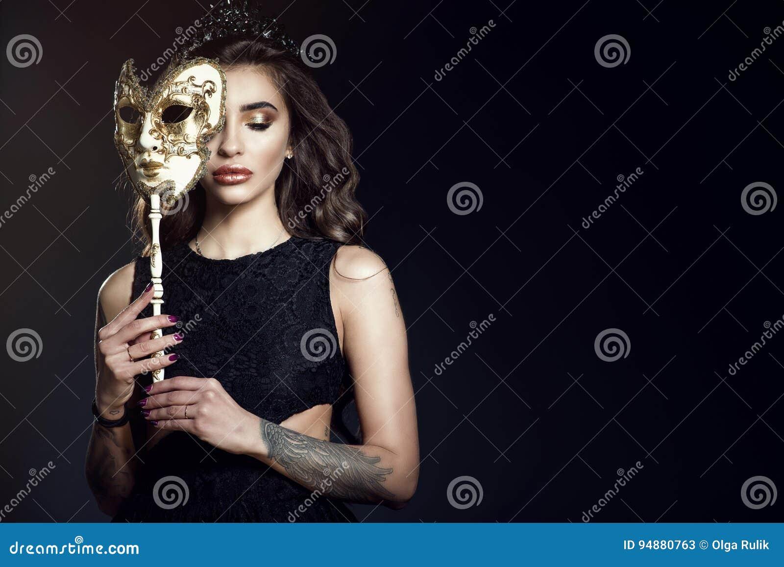 Mooie dame met gesloten ogen die de helft van haar gezicht achter het Venetiaanse masker verbergen