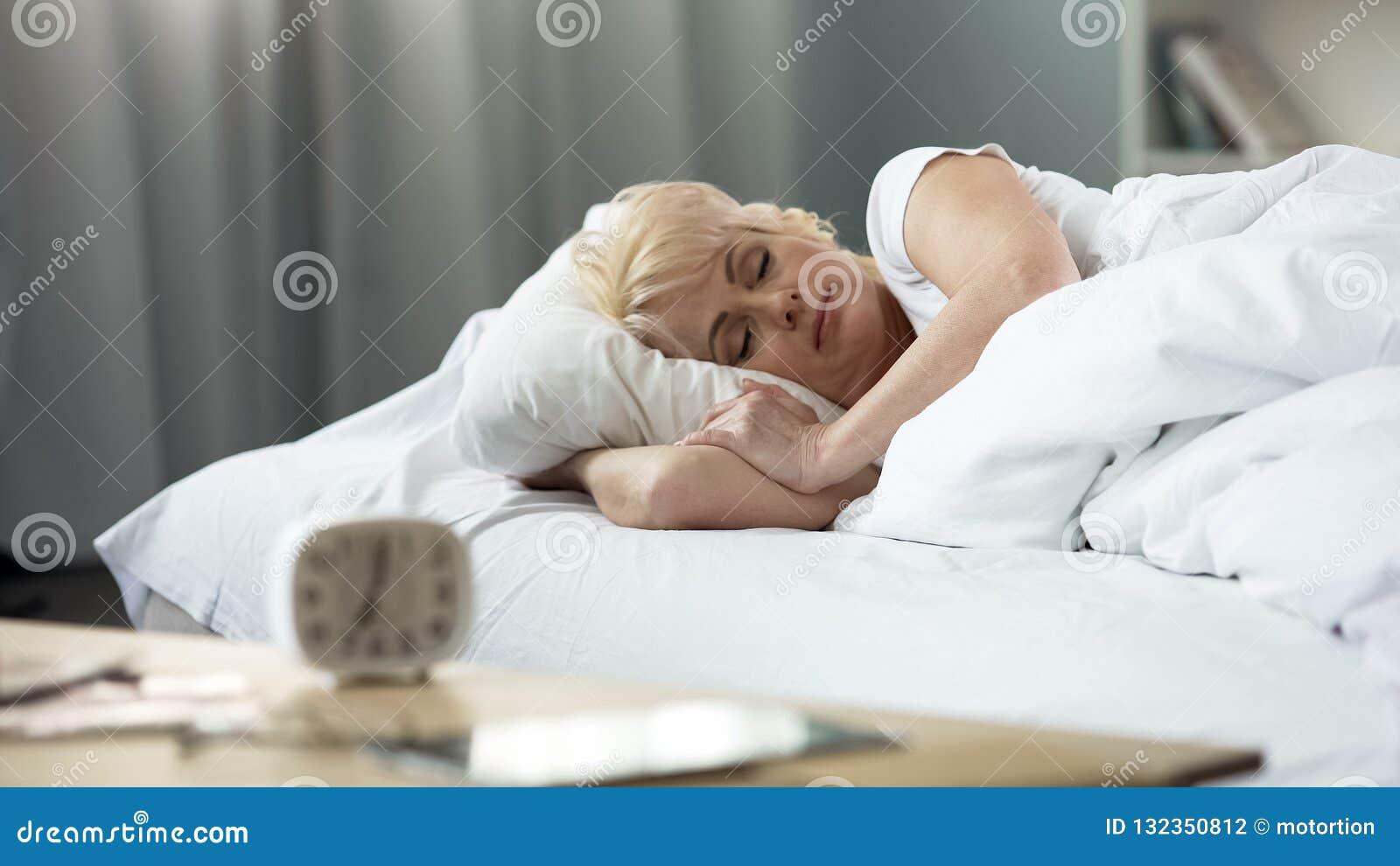 Mooie dameslaap op middelbare leeftijd in bed, slaapcyclus, vreedzame rust, gezondheid