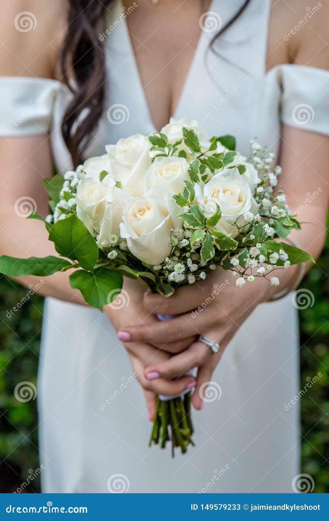 Mooie die wit nam boeket met de adem van de baby door een bruid met donker haar wordt gehouden die een witte huwelijkskleding en
