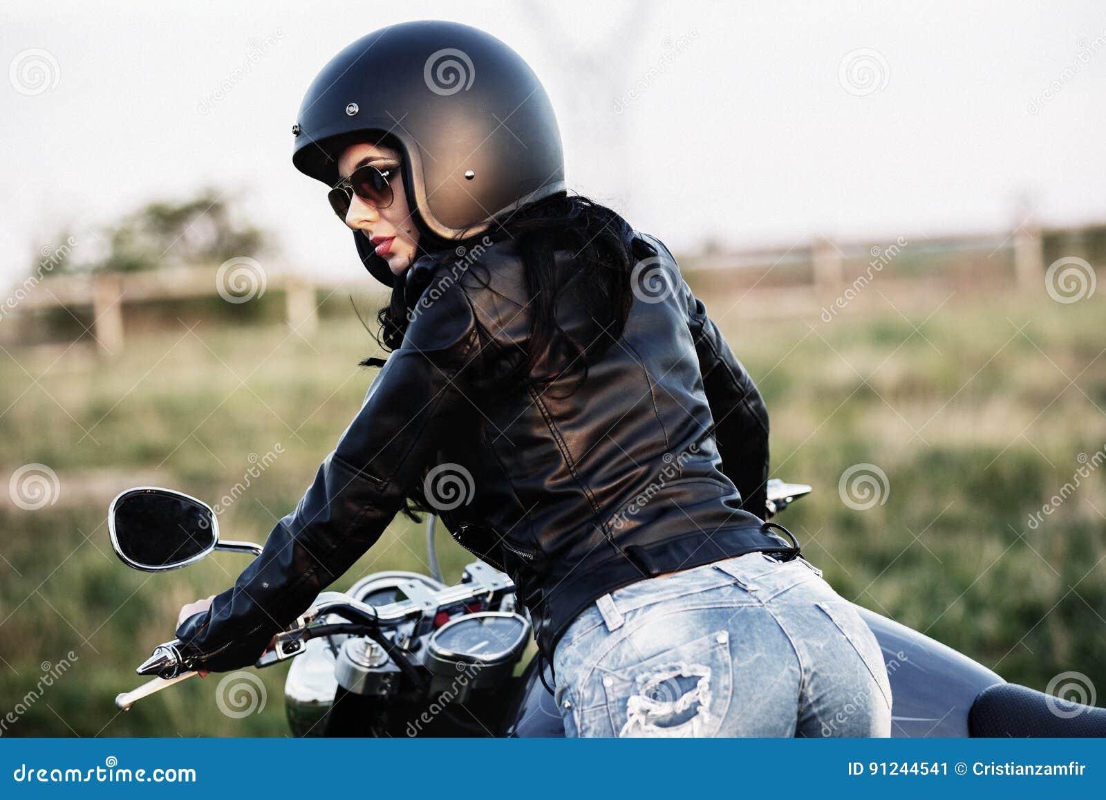Mooie donkerbruine vrouw met een klassieke motorfiets c
