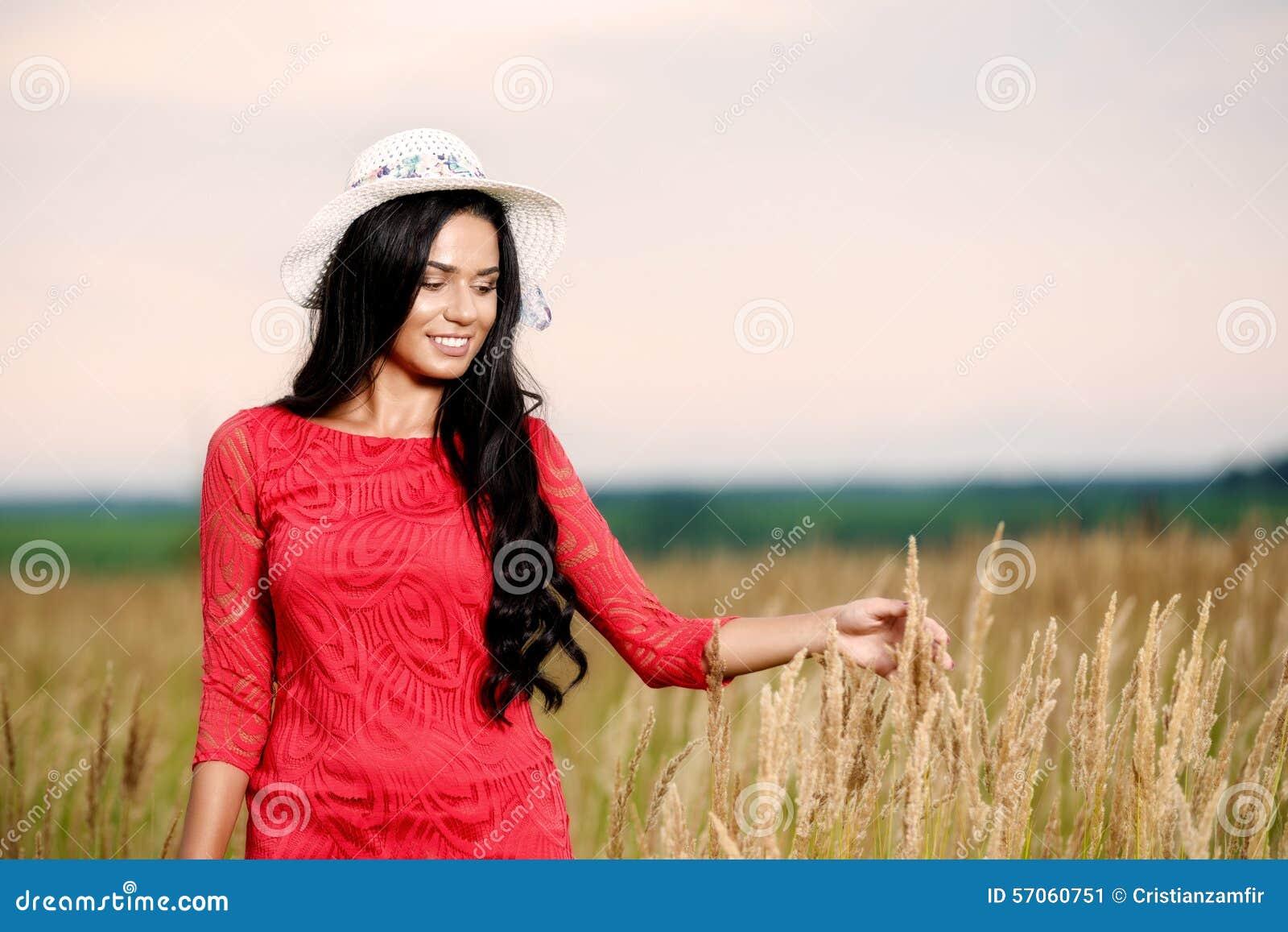 Mooie donkerbruine vrouw met een rode kleding op een gebied