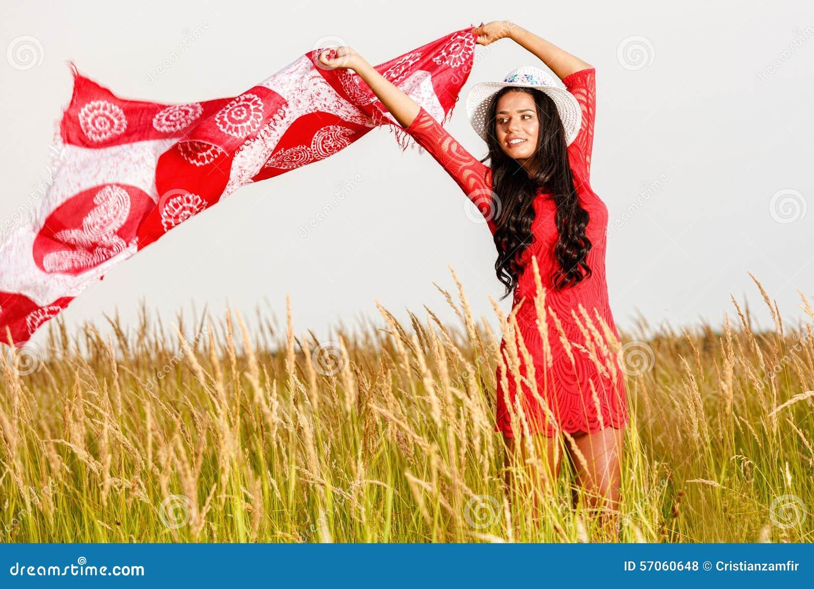 Mooie donkerbruine vrouw met een sjaal op een gebied