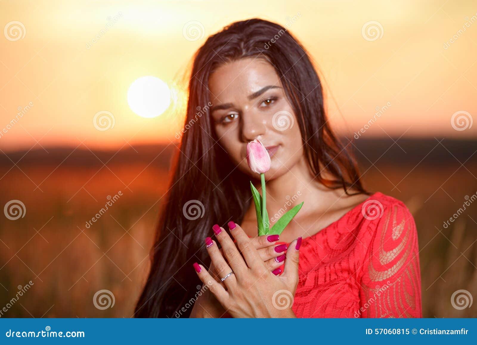 Mooie donkerbruine vrouw in rode kleding met tulpen in handen op a