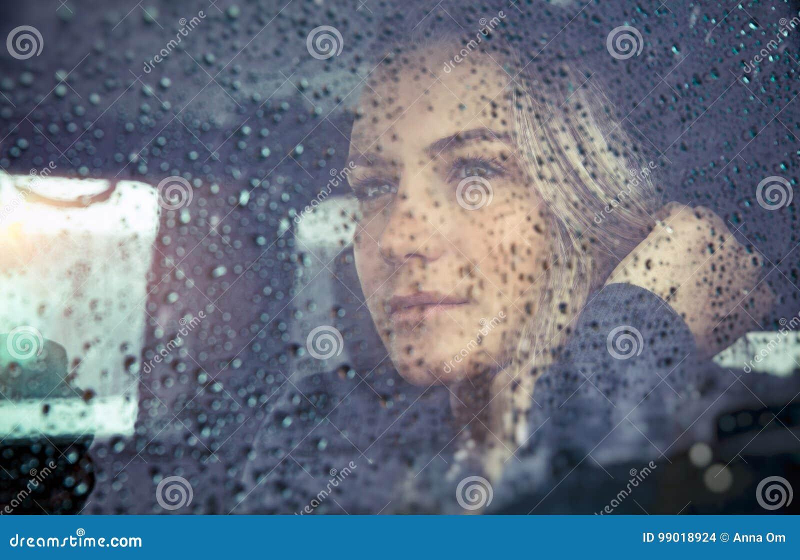 Mooie droevige vrouw in de auto