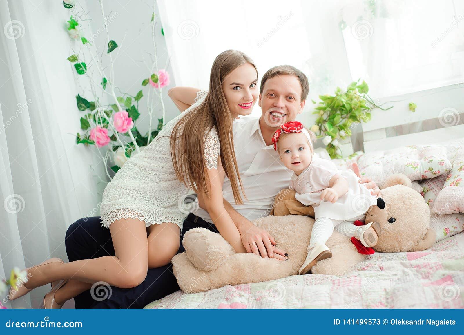 Mooie familie die en, bij camera stellen, en elkaar voor familiefoto koesteren glimlachen lachen