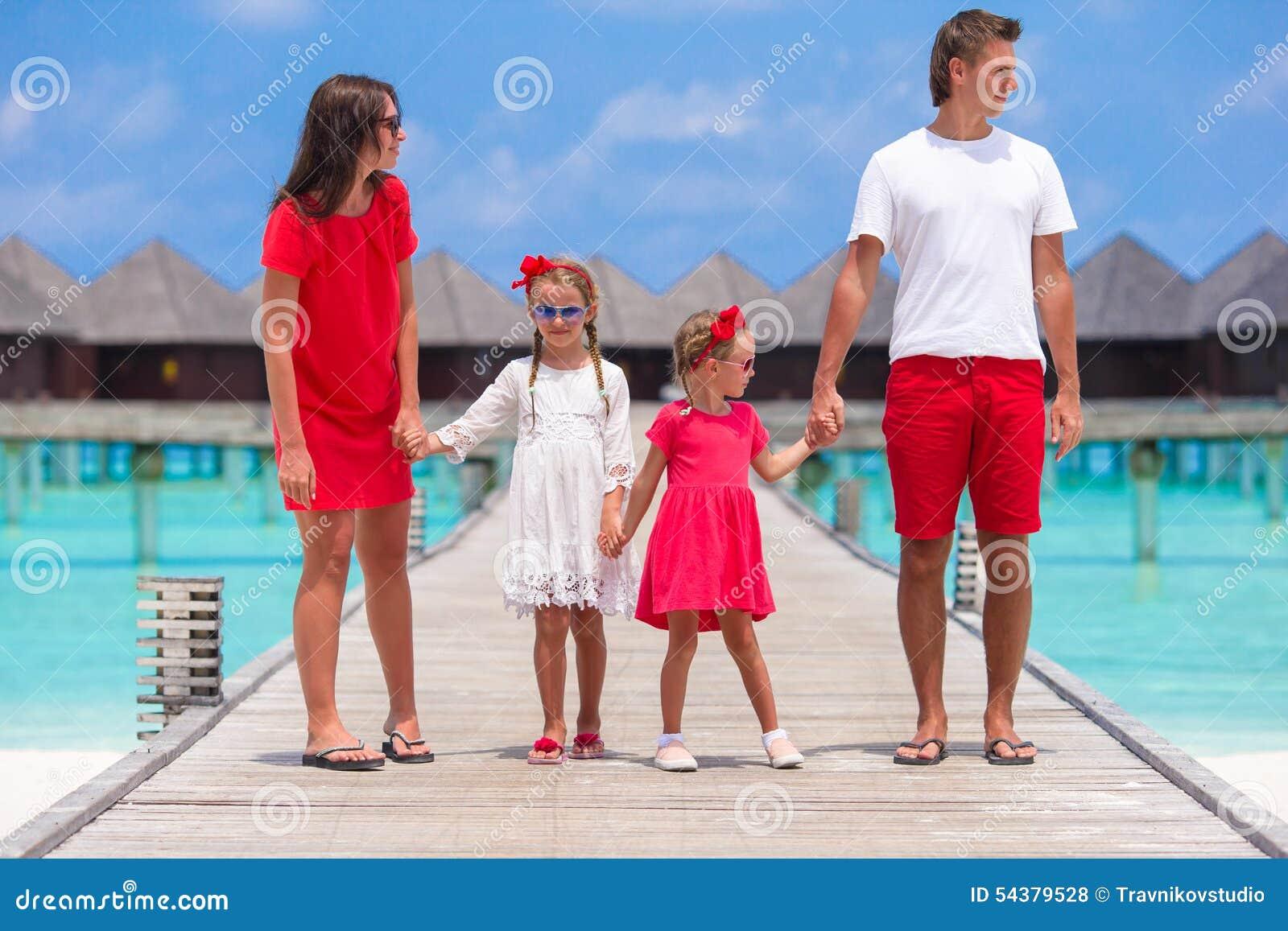 Mooie familie in rood die pret op houten pier hebben