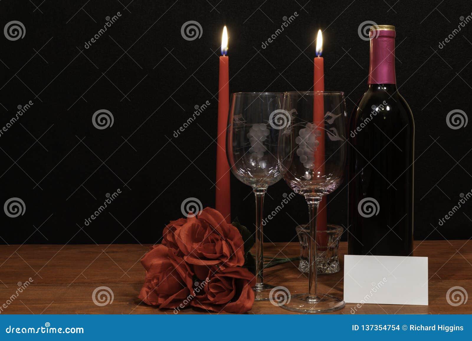 Mooie geëtste wijnglazen en fles van rode wijn, rode kaarsen en rode rozen op houten lijst met naamplaatje op donkere achtergrond