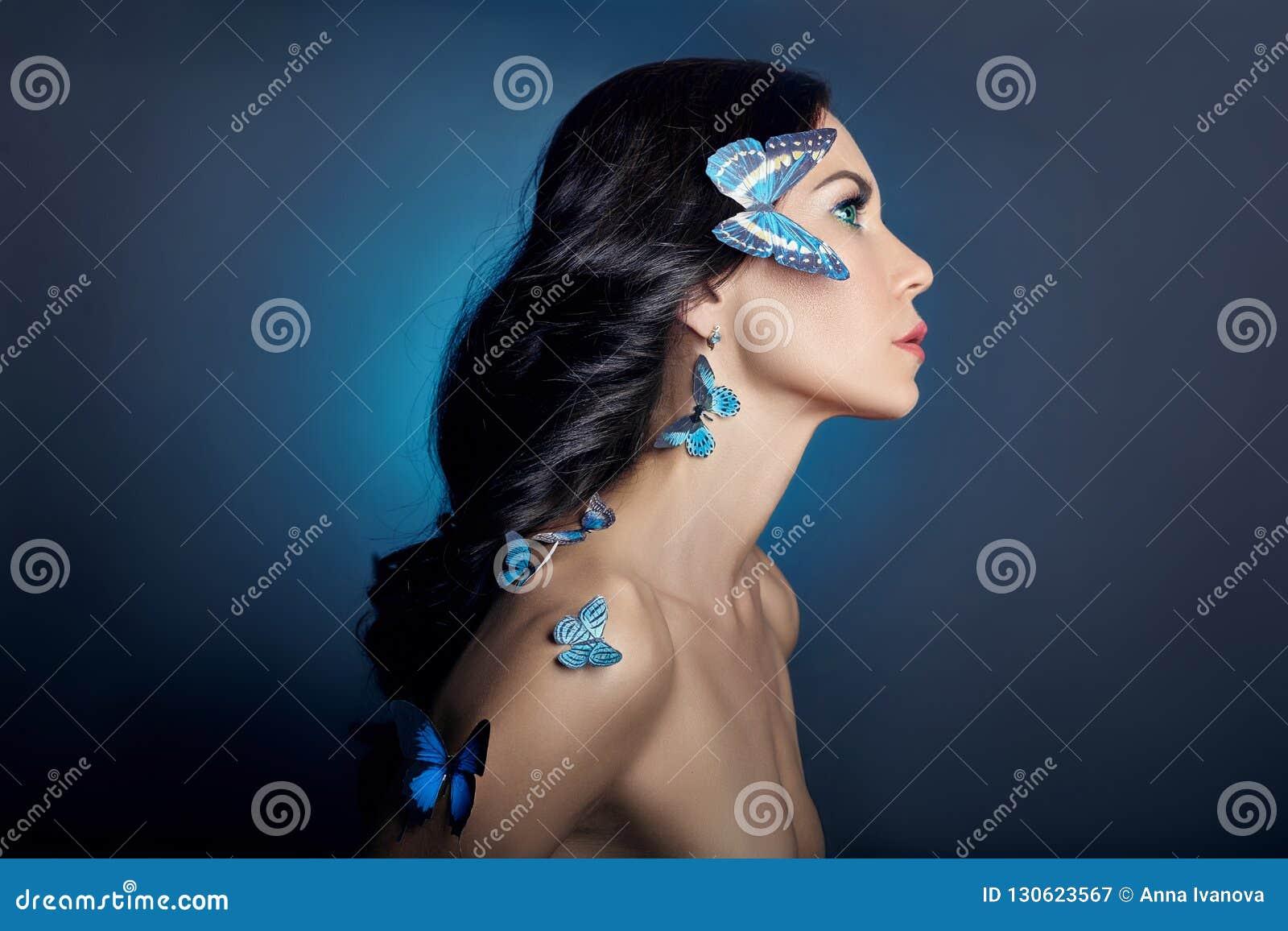 Mooie geheimzinnige vrouw met vlinders blauwe kleur op haar gezicht, brunette en document kunstmatige blauwe vlinders op de meisj