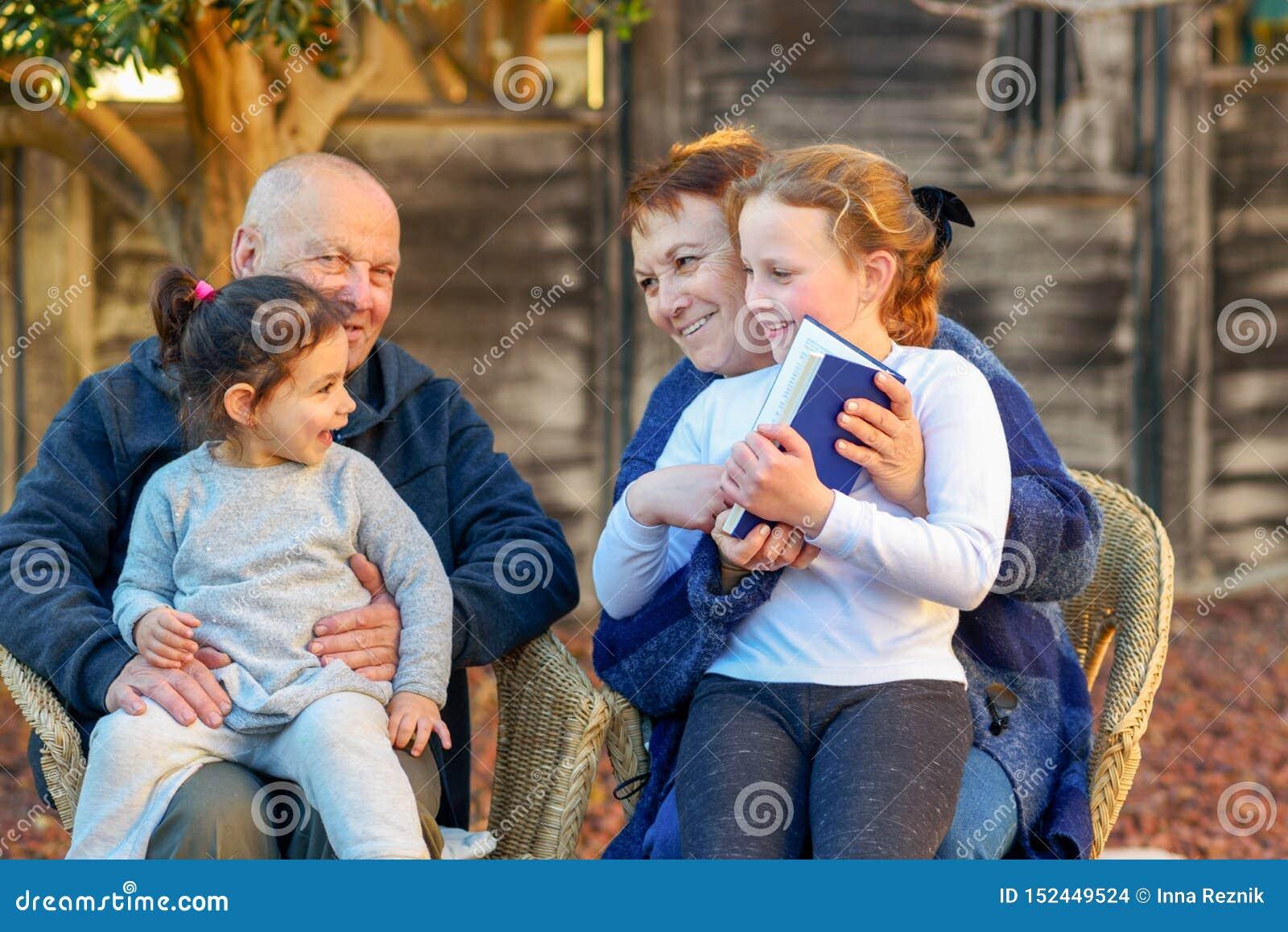 Mooie Gelukkige Oude paar en kleindochters die een boek samen in de aard lezen bij zonsondergang