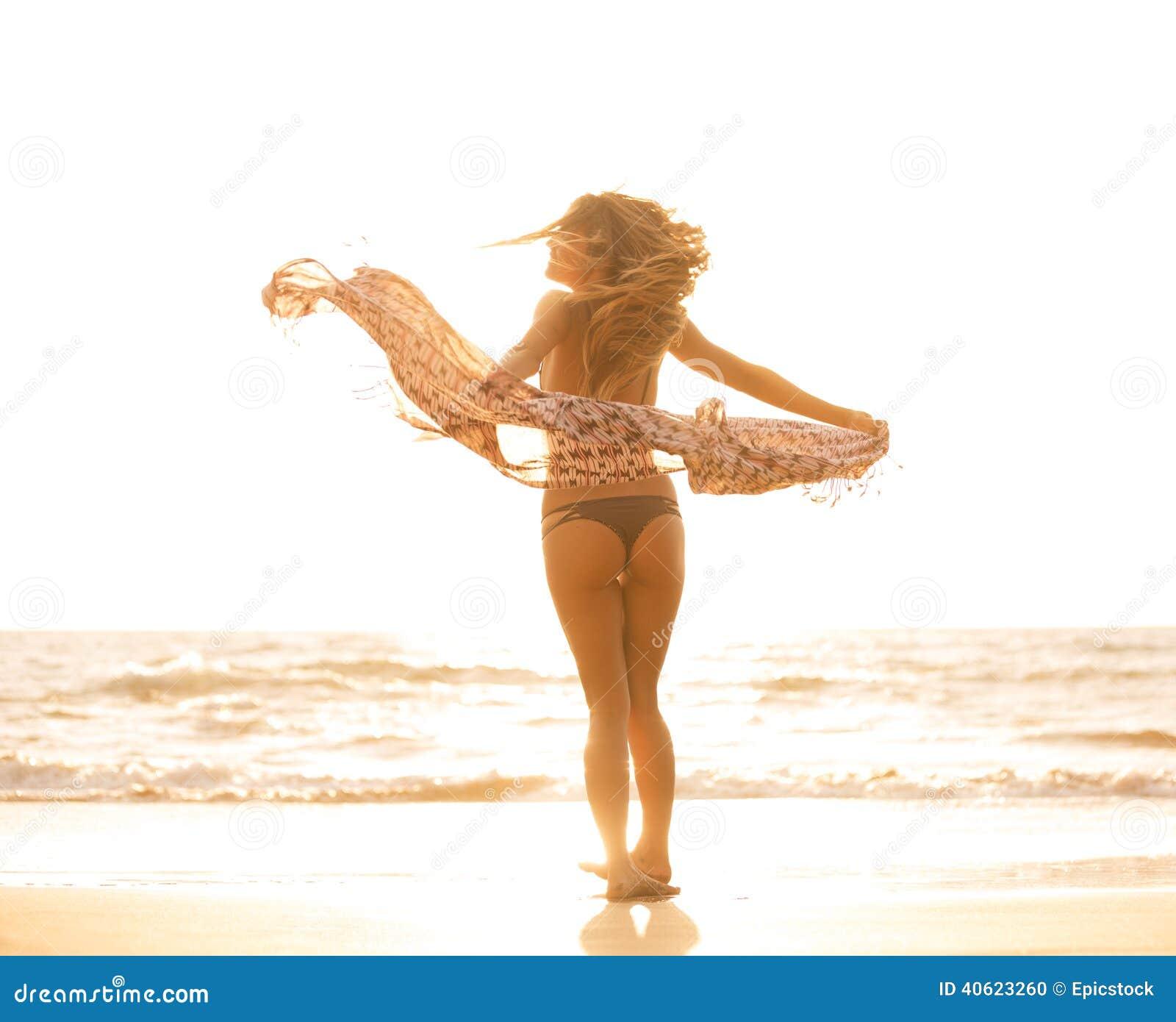 Mooie gelukkige vrouw op strand bij zonsondergang