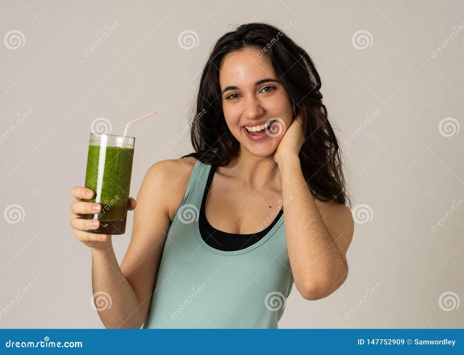 Mooie geschikte sport Latijnse vrouw die gezonde verse groentesmoothie drinken die groot en gezond voelen