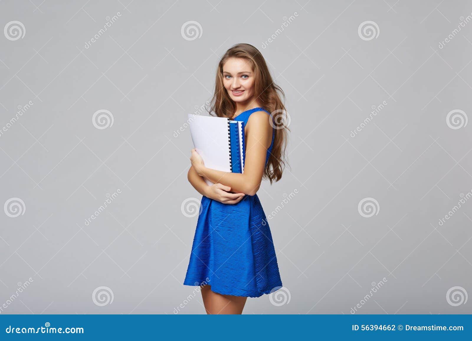 Mooie glimlachende bedrijfsvrouw, met documenten, op een grijze rug
