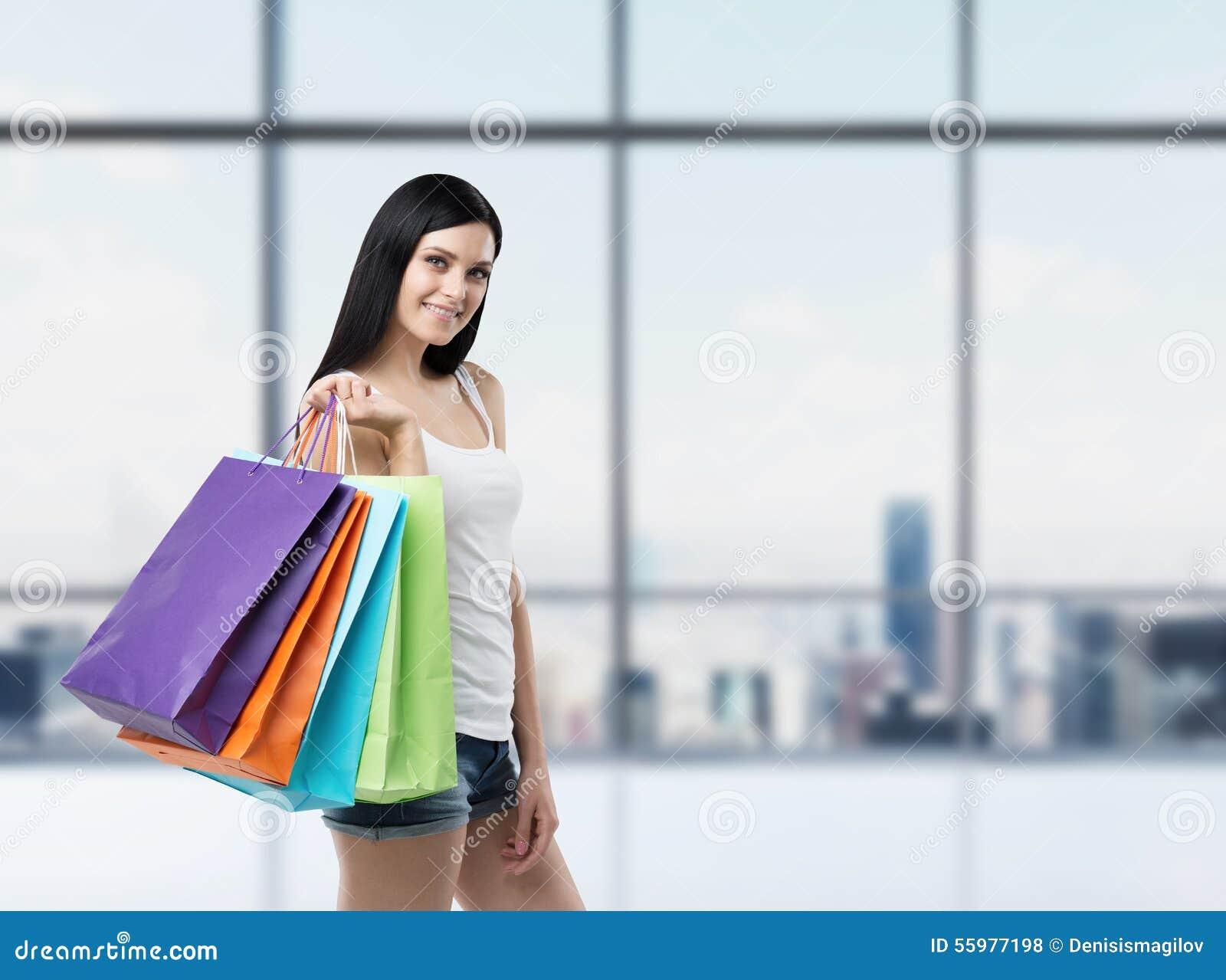Mooie glimlachende donkerbruine vrouw met de kleurrijke het winkelen zakken van de buitensporige winkels