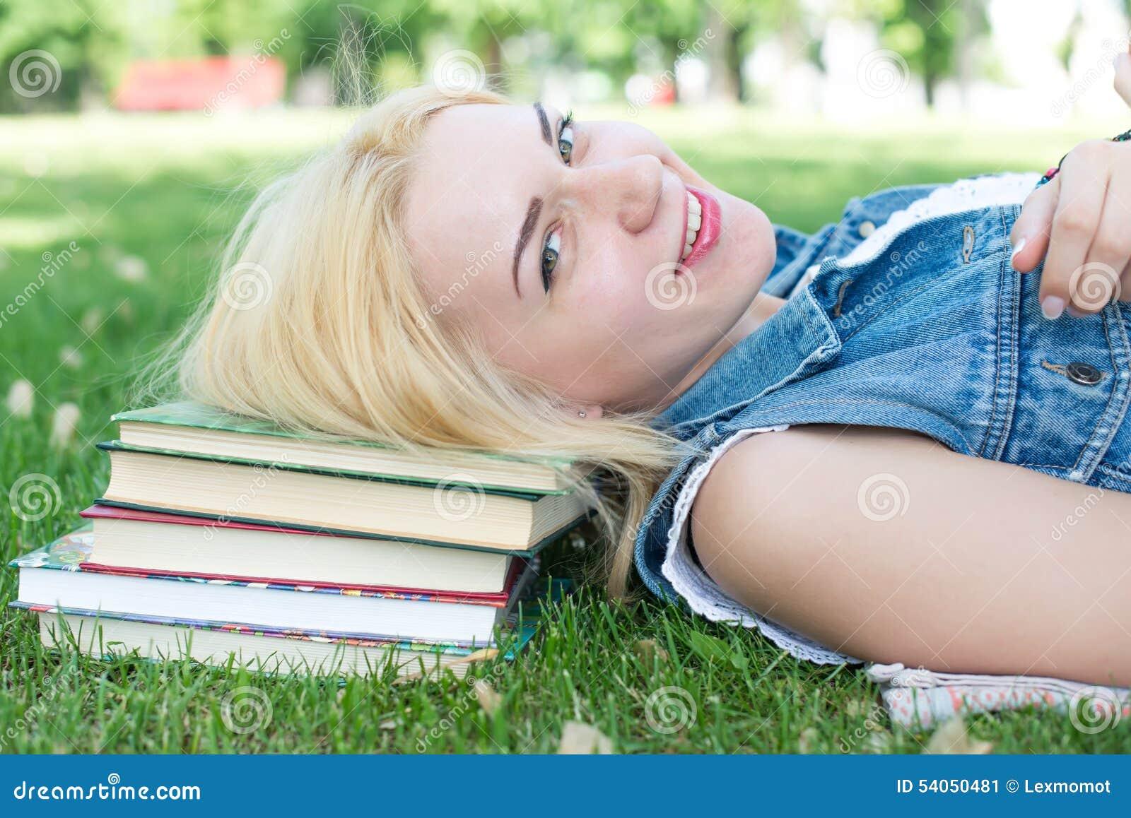 Mooie glimlachende jonge vrouw die op gras liggen