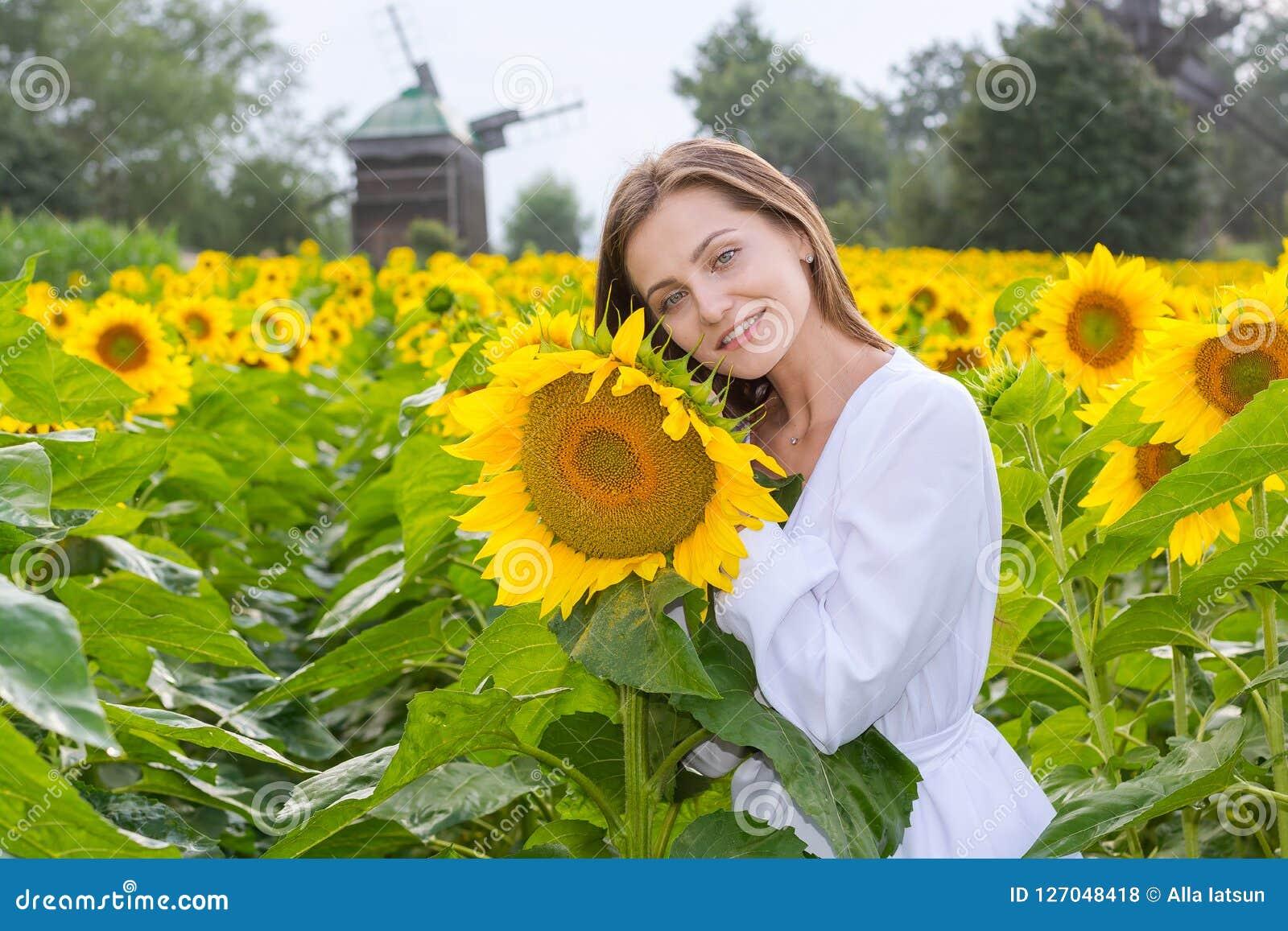 Mooie glimlachende jonge vrouw in een witte overhemdstribunes in fie