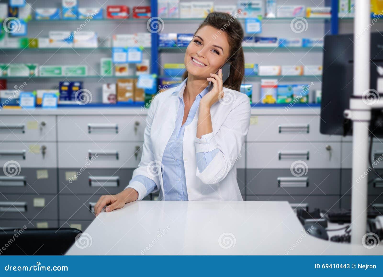 Mooie glimlachende jonge vrouwenapotheker die op de celtelefoon spreken in apotheek