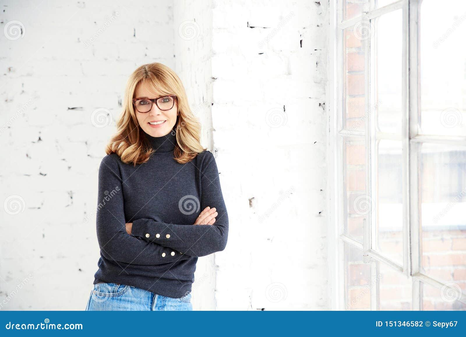 Mooie glimlachende vrouw die zich met gekruiste wapens bevinden terwijl het ontspannen bij het venster