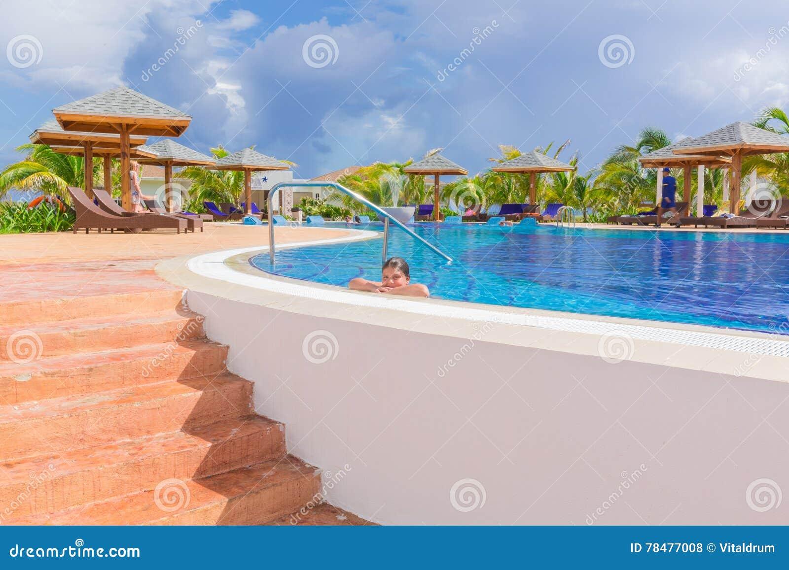 Mooie het uitnodigen mening van comfortabel comfortabel zwembad met het geglimlachte meisje ontspannen zwemmend en genietend van