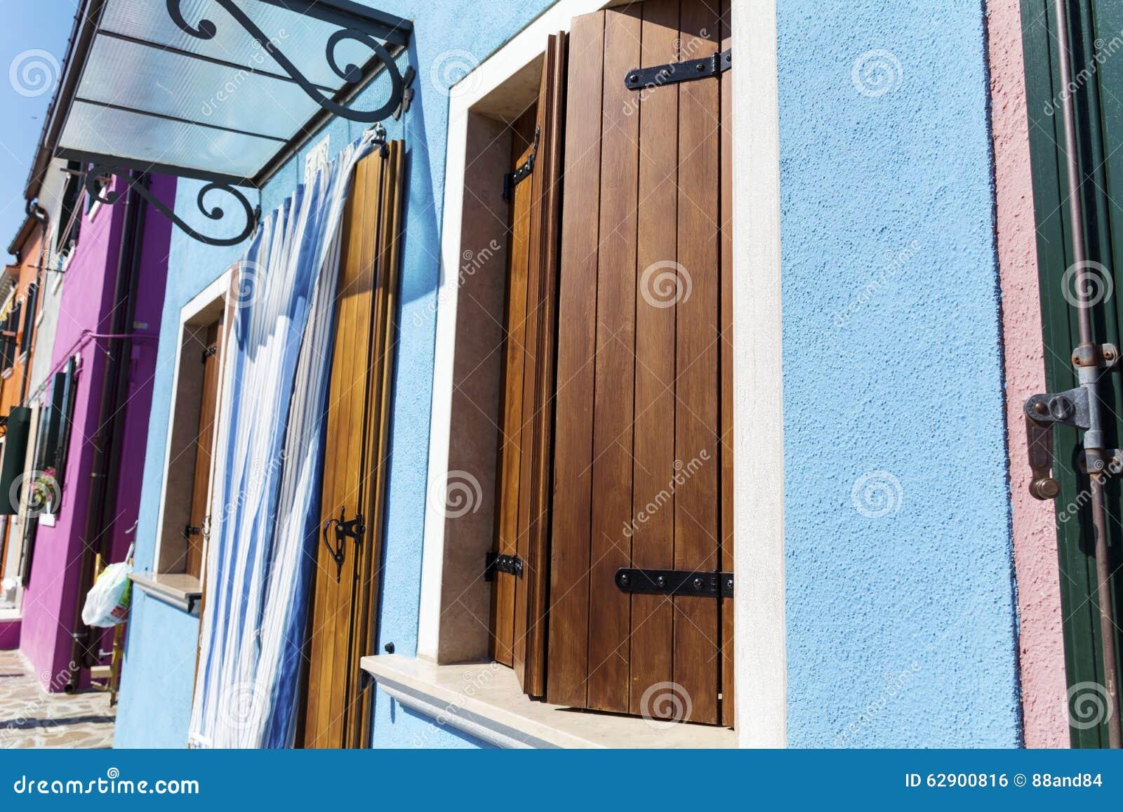 blauwe huisvoorgevel met houten deur blauwe gordijnen en houten blinden in burano eiland veneti itali