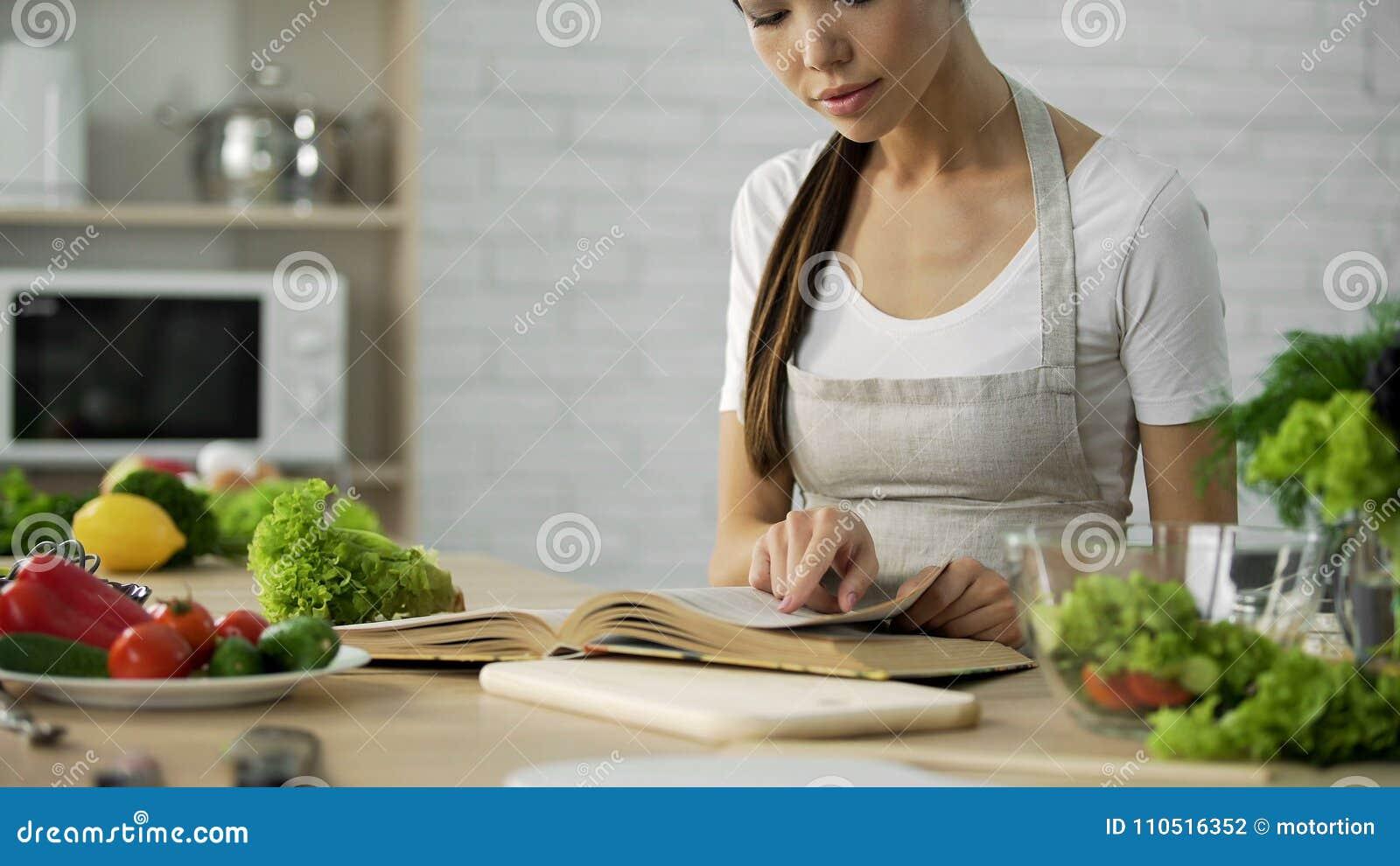 Mooie huisvrouw die familie traditioneel recept in oma kokend boek zoeken
