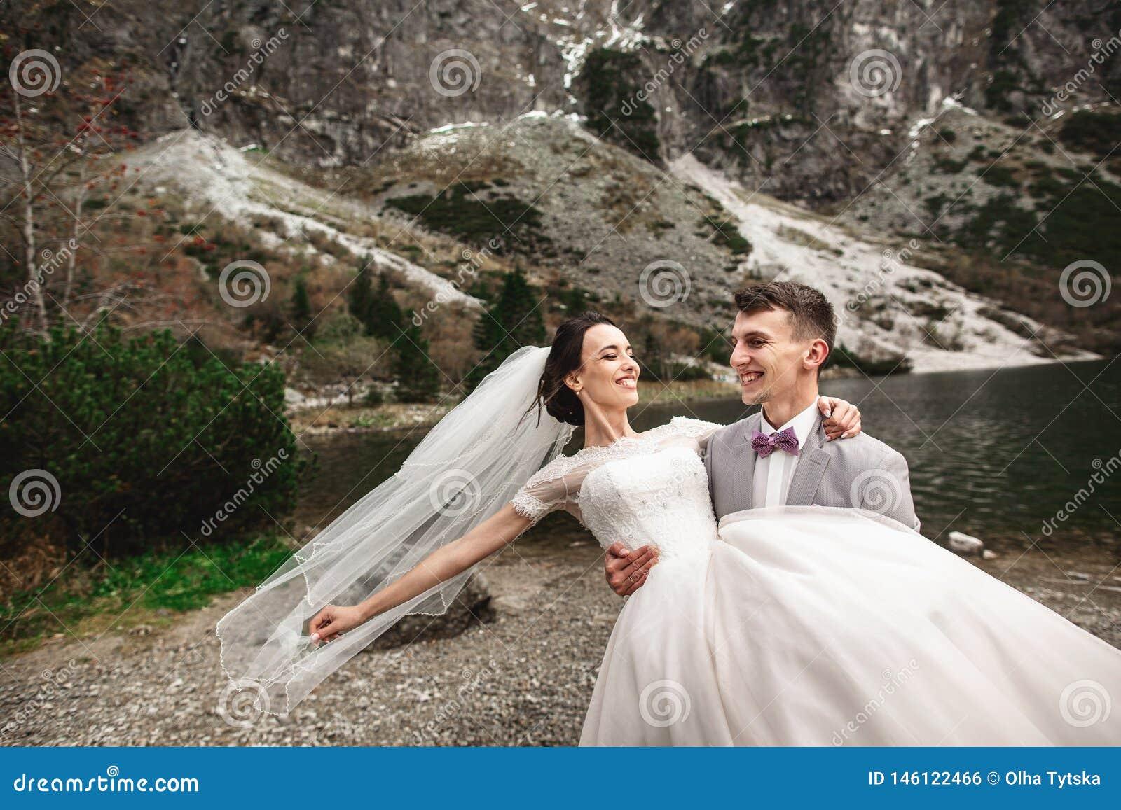 Mooie huwelijksphotosession De bruidegom omcirkelt zijn jonge bruid, op de kust van het meer Morskie Oko polen